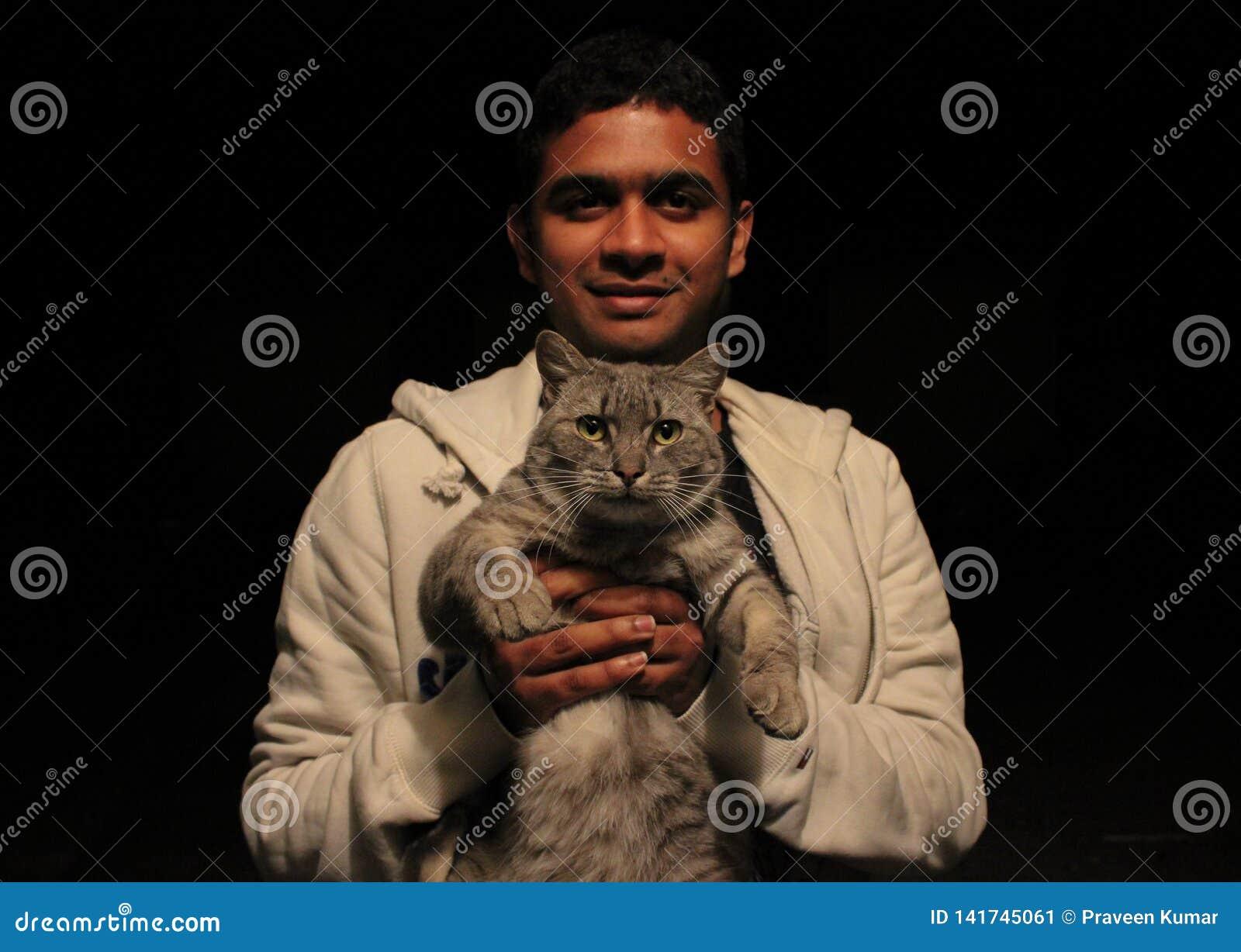 Hombre asiático joven que sostiene un gato con el amor y la sonrisa, mirando la cámara con el fondo negro llano