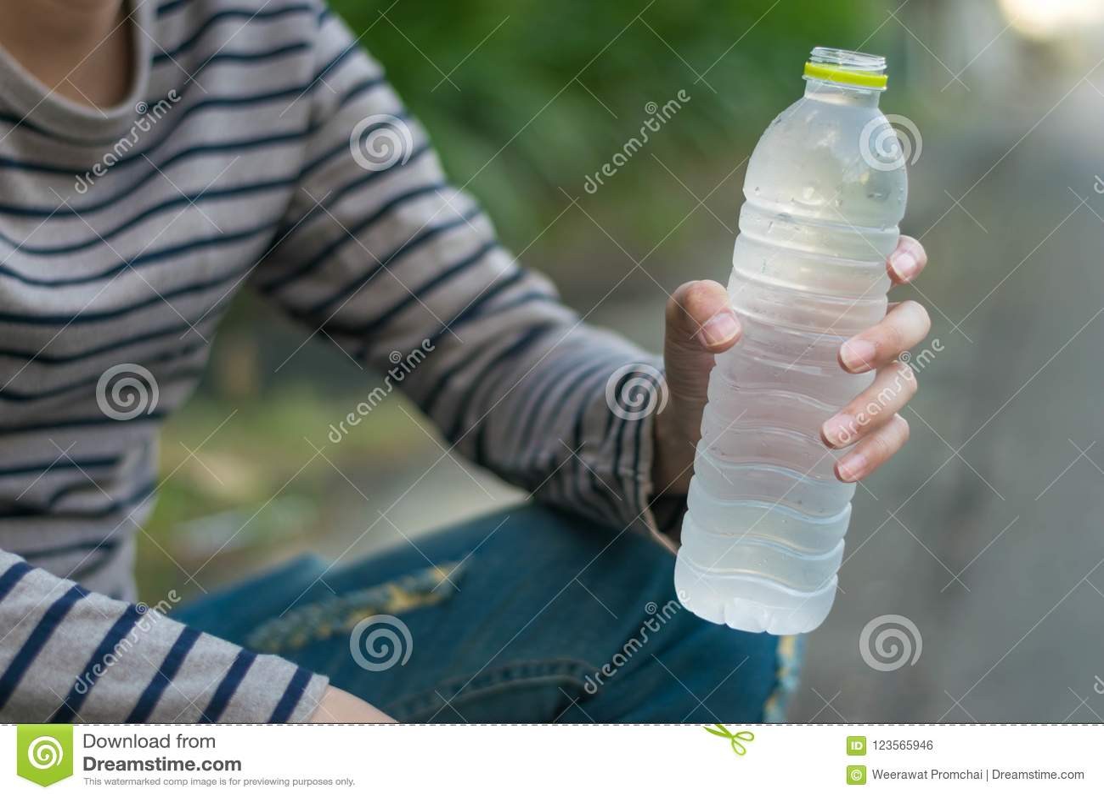 Hombre asiático que sienta y que sostiene la botella de agua
