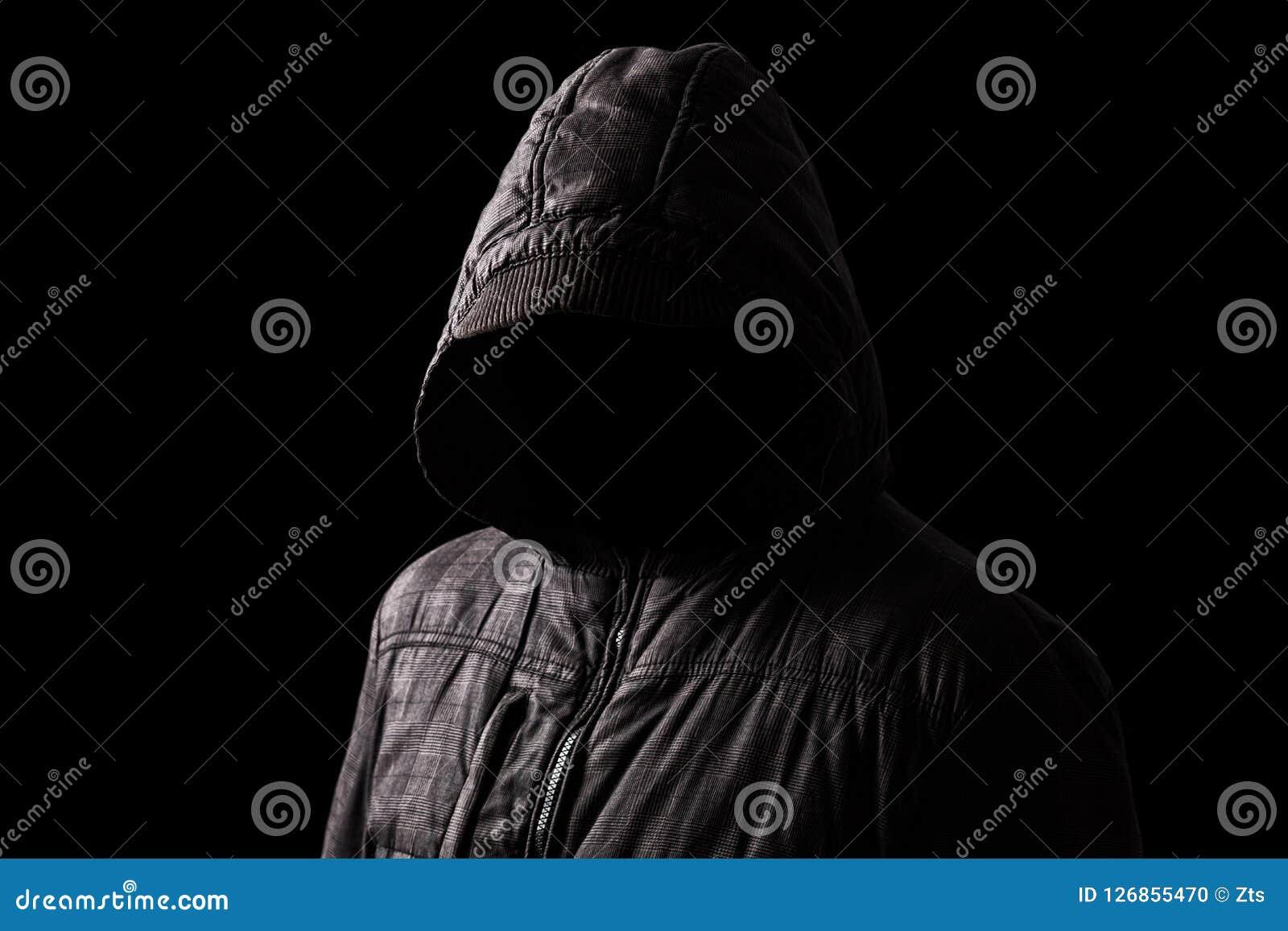 Hombre asustadizo y espeluznante que oculta en las sombras, con la cara y la identidad ocultadas con la capilla