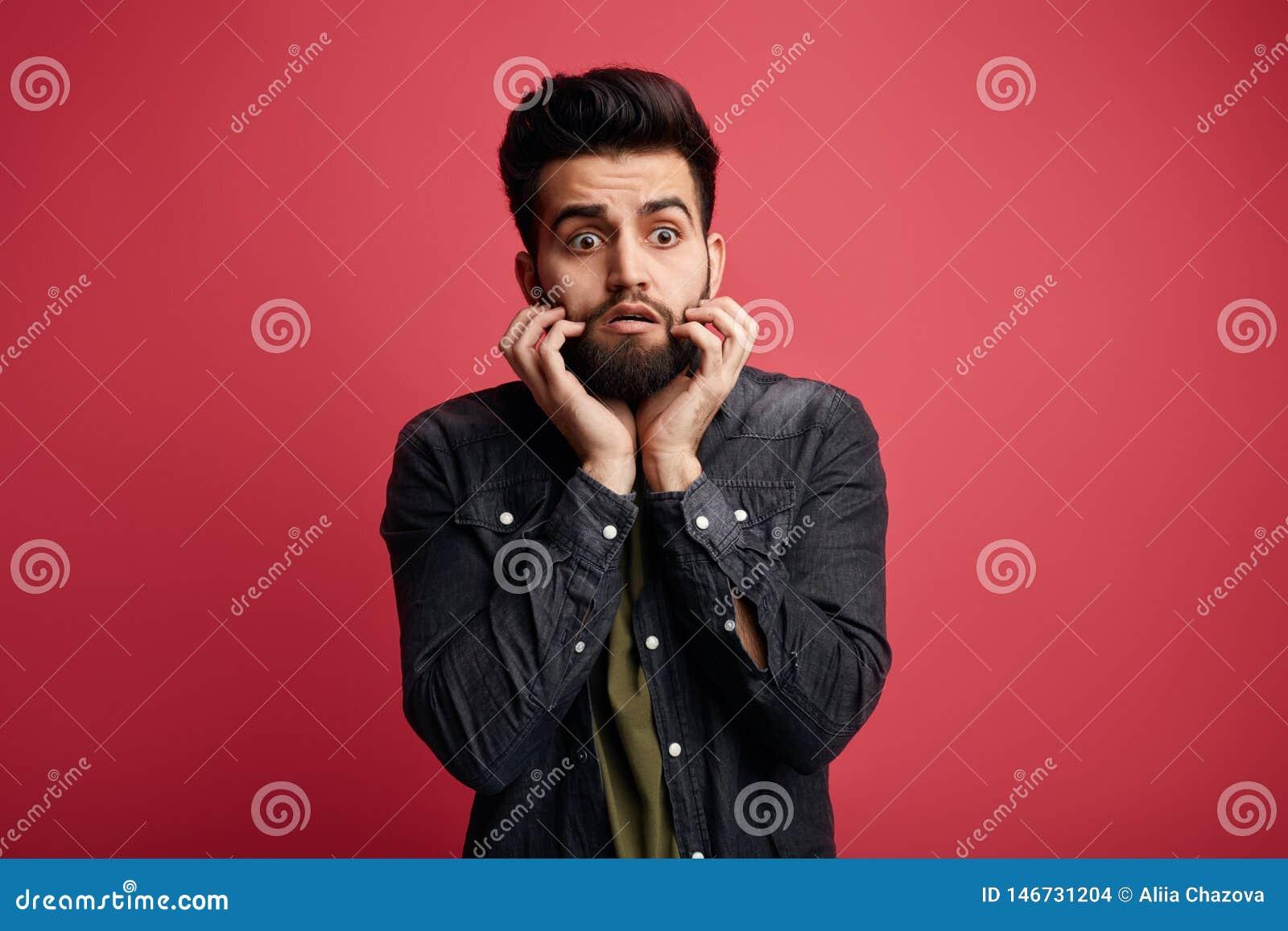 Hombre asustado hermoso con los fingeres en su boca, teniendo miedo algo,