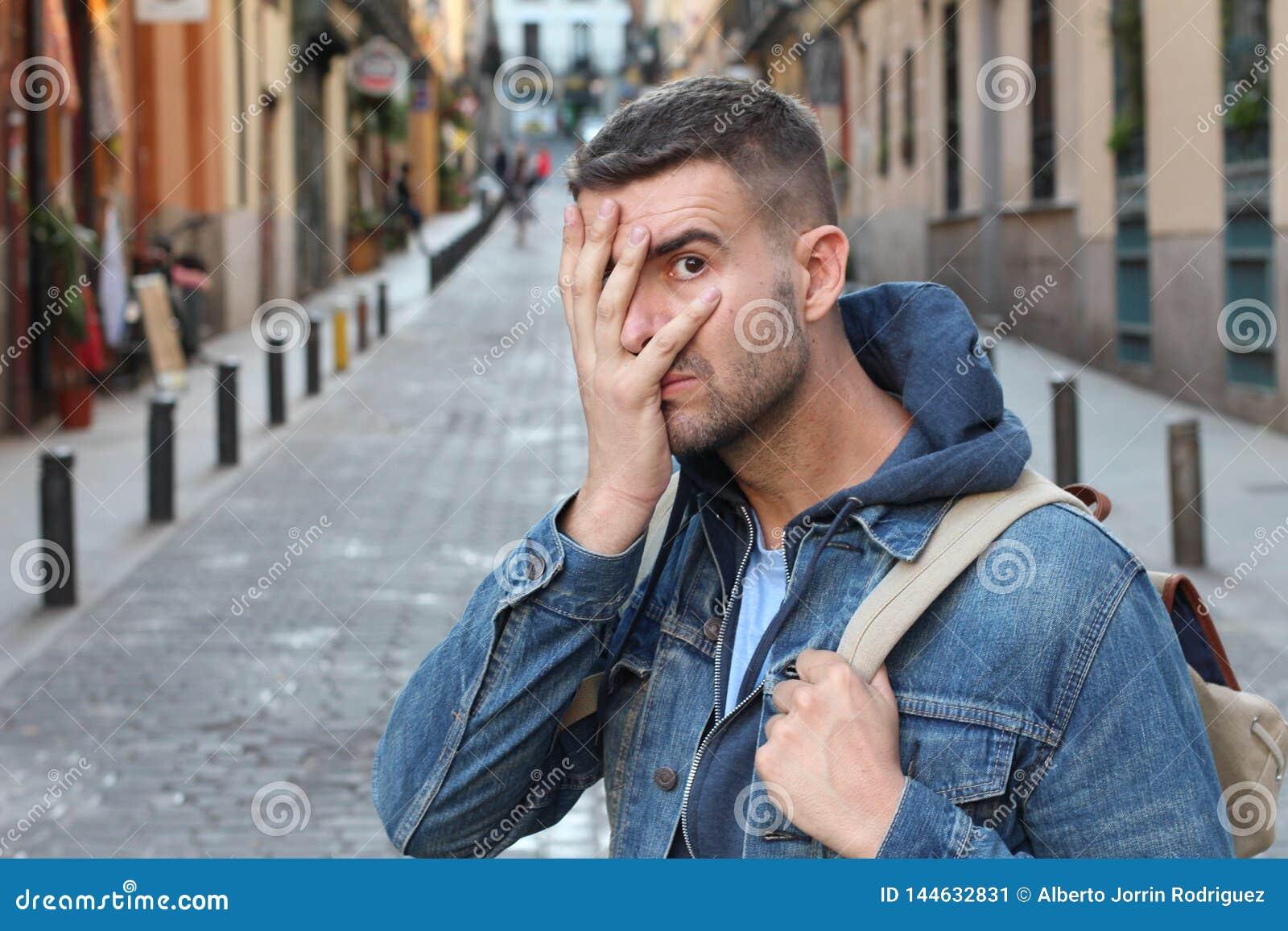 Hombre asustado que oculta su cara al aire libre