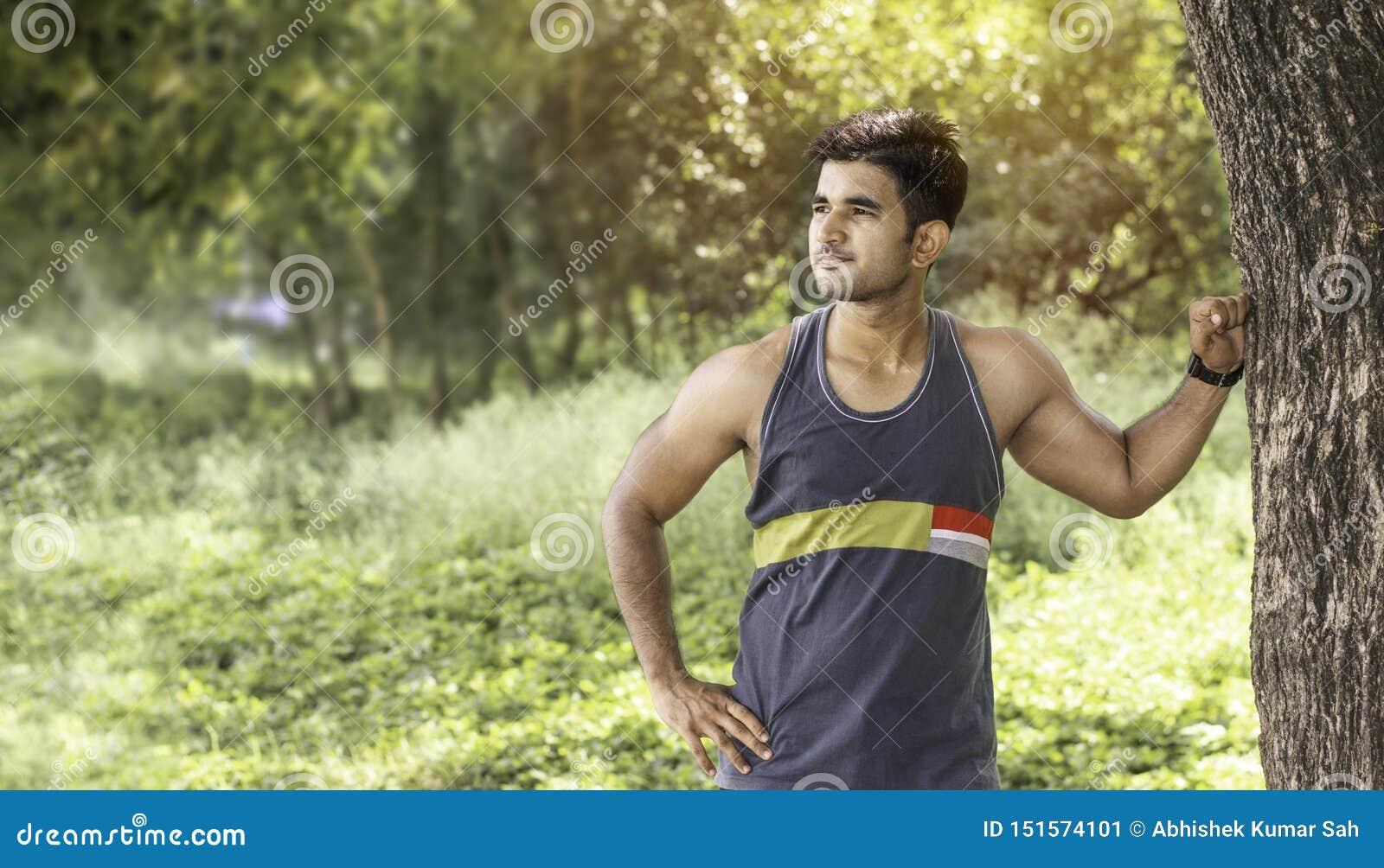 Hombre atlético joven que toma una rotura debajo de árbol durante activar desafiador al aire libre