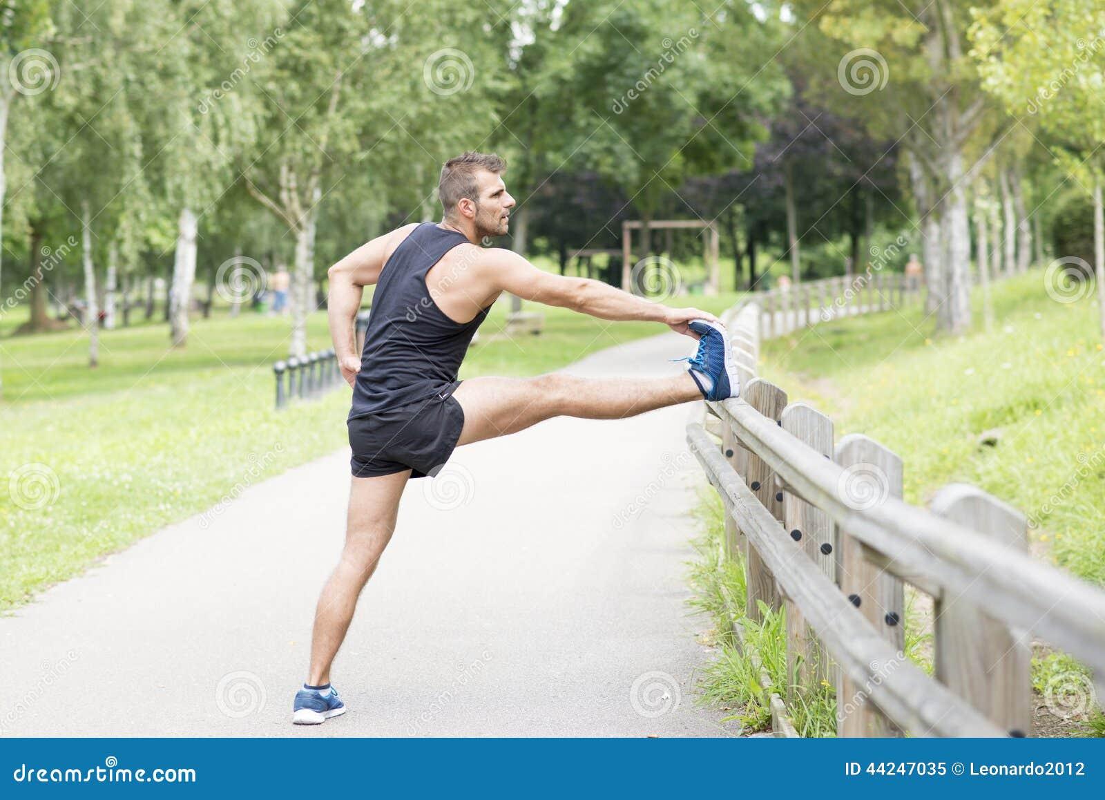Hombre atlético que hace estiramientos antes de ejercitar, al aire libre