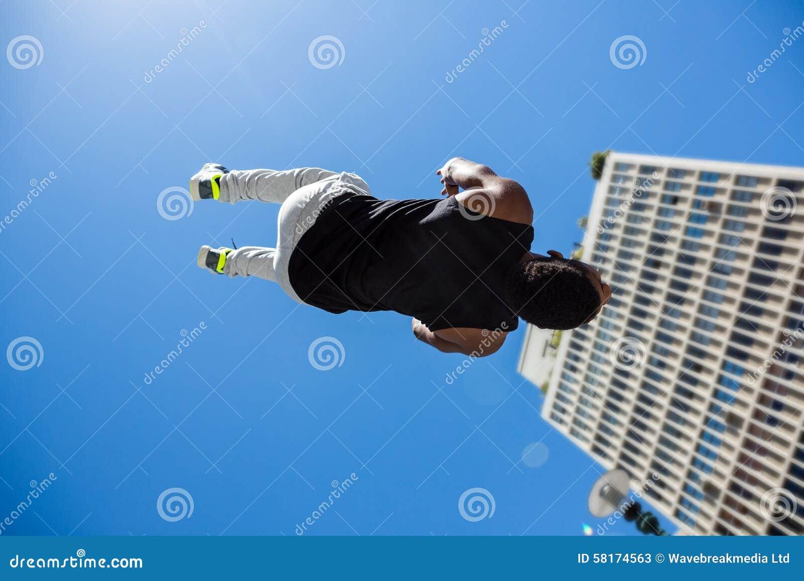 Hombre atlético que hace salto mortal hacia atrás en la ciudad