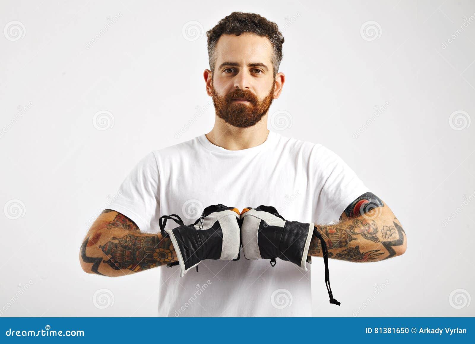 Hombre atractivo joven que demuestra guantes de la snowboard