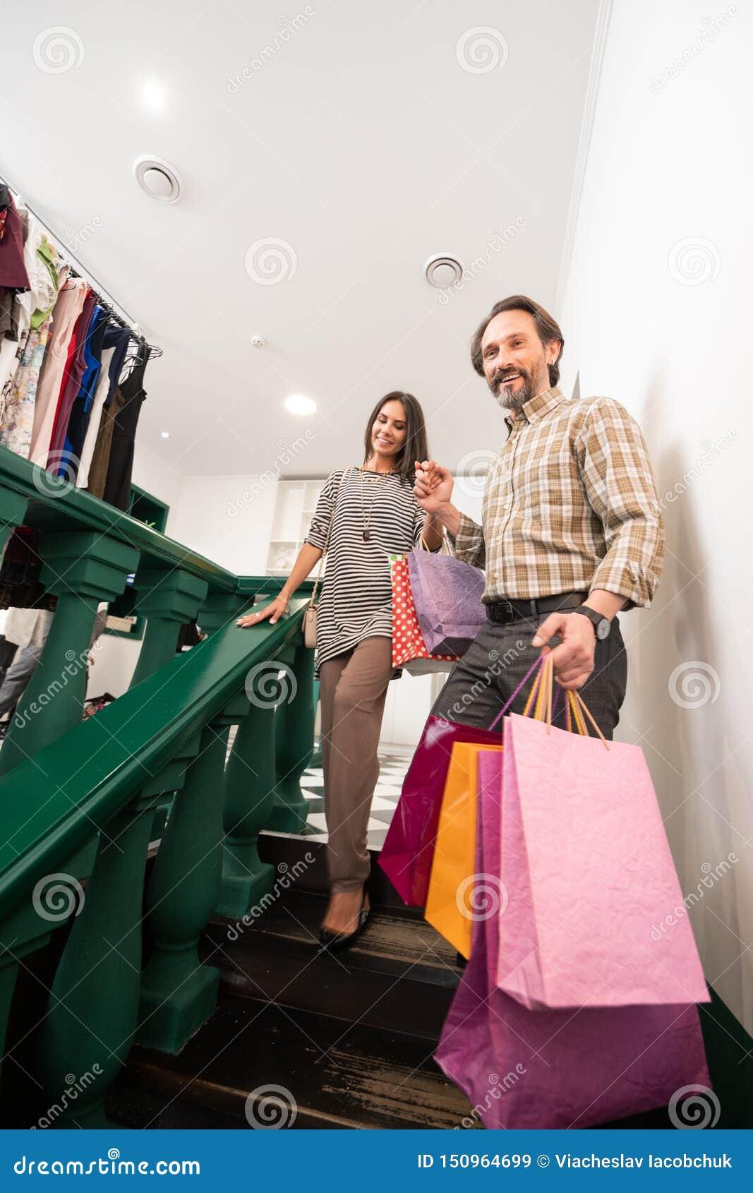 Hombre atractivo que ayuda a la señora atractiva con los bolsos de compras