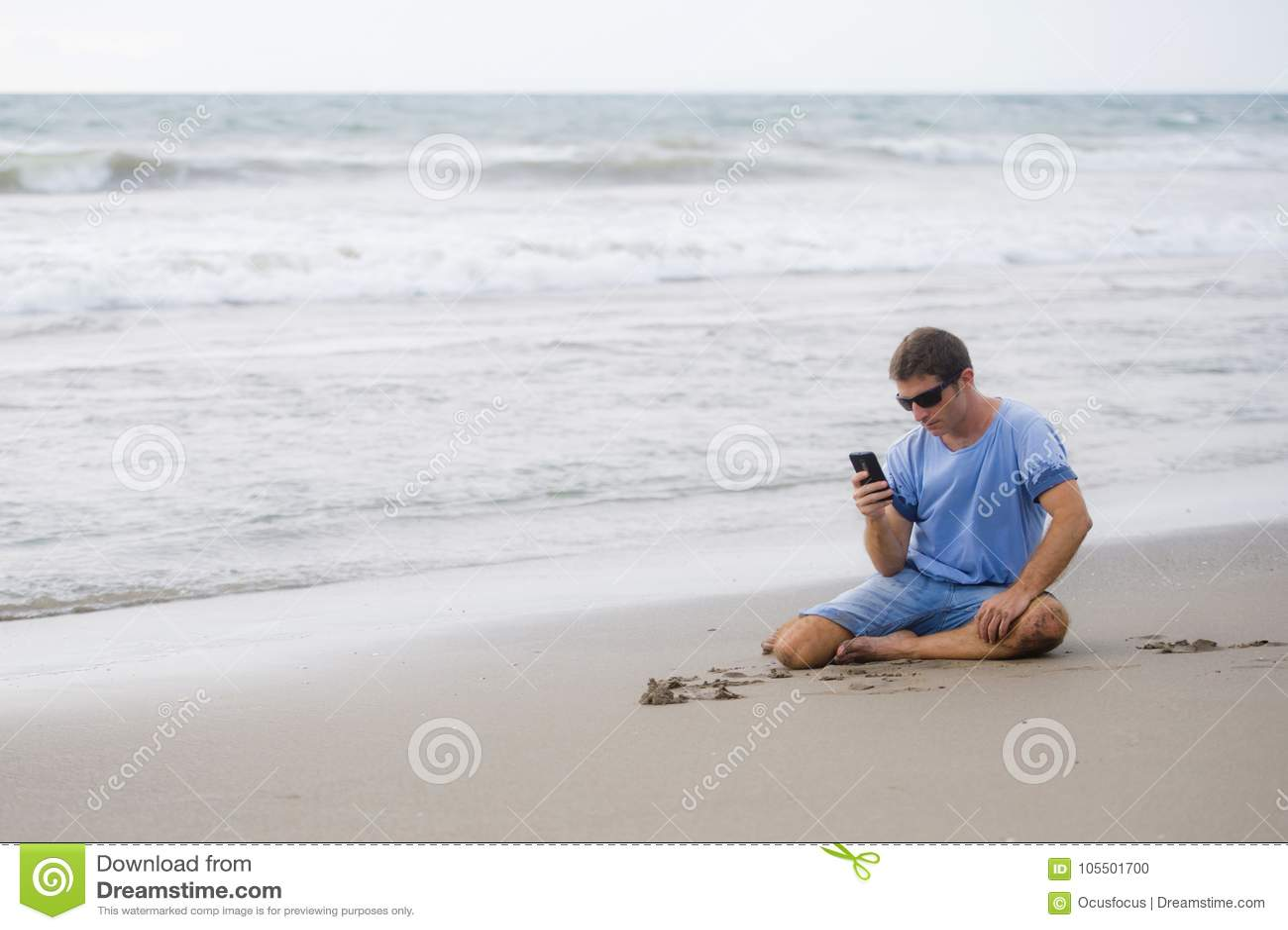 Hombre atractivo y hermoso en su 30s que se sienta en la arena relajada en la playa que ríe delante del mar que manda un SMS en p