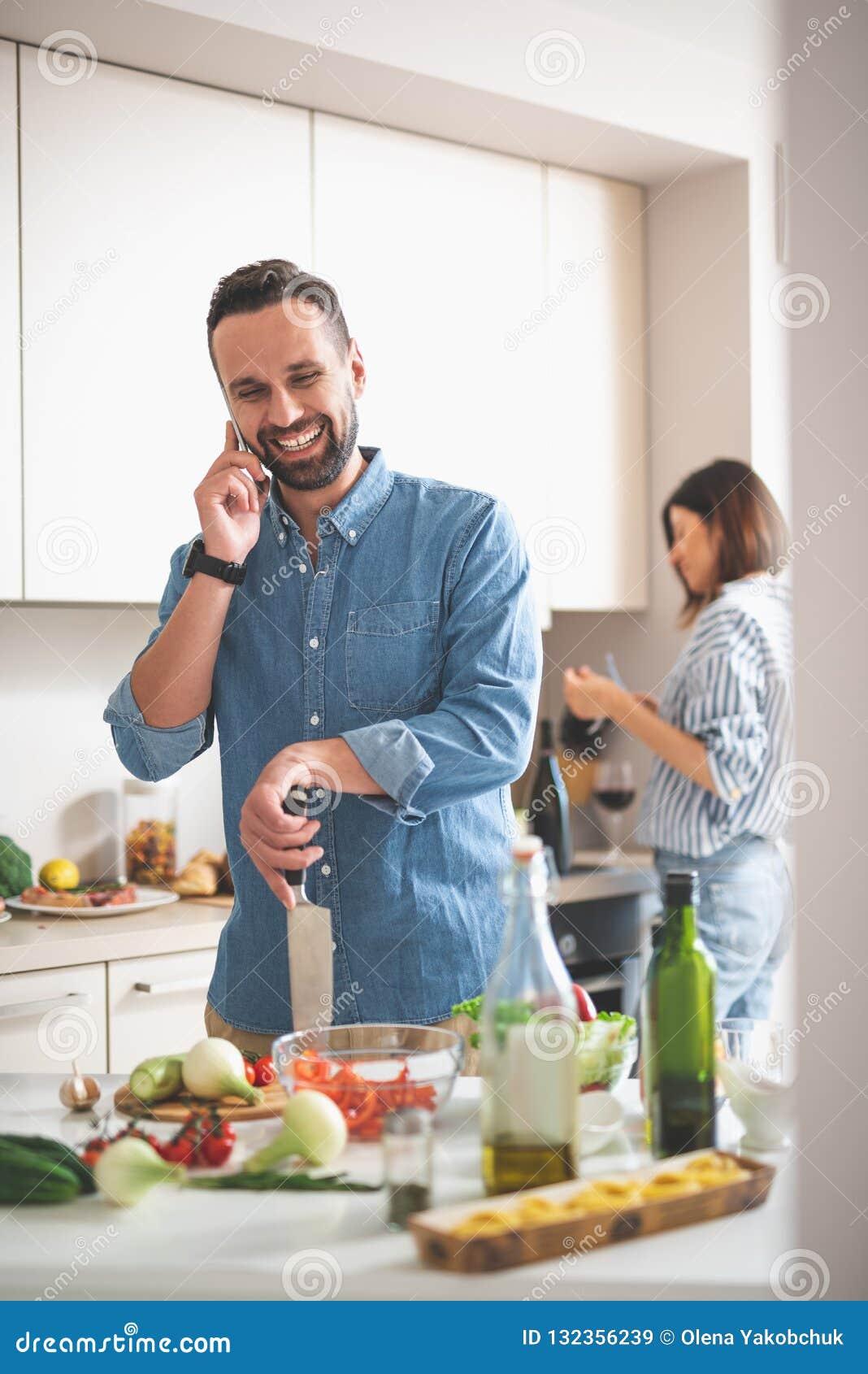 Hombre barbudo alegre que habla en el teléfono móvil en cocina