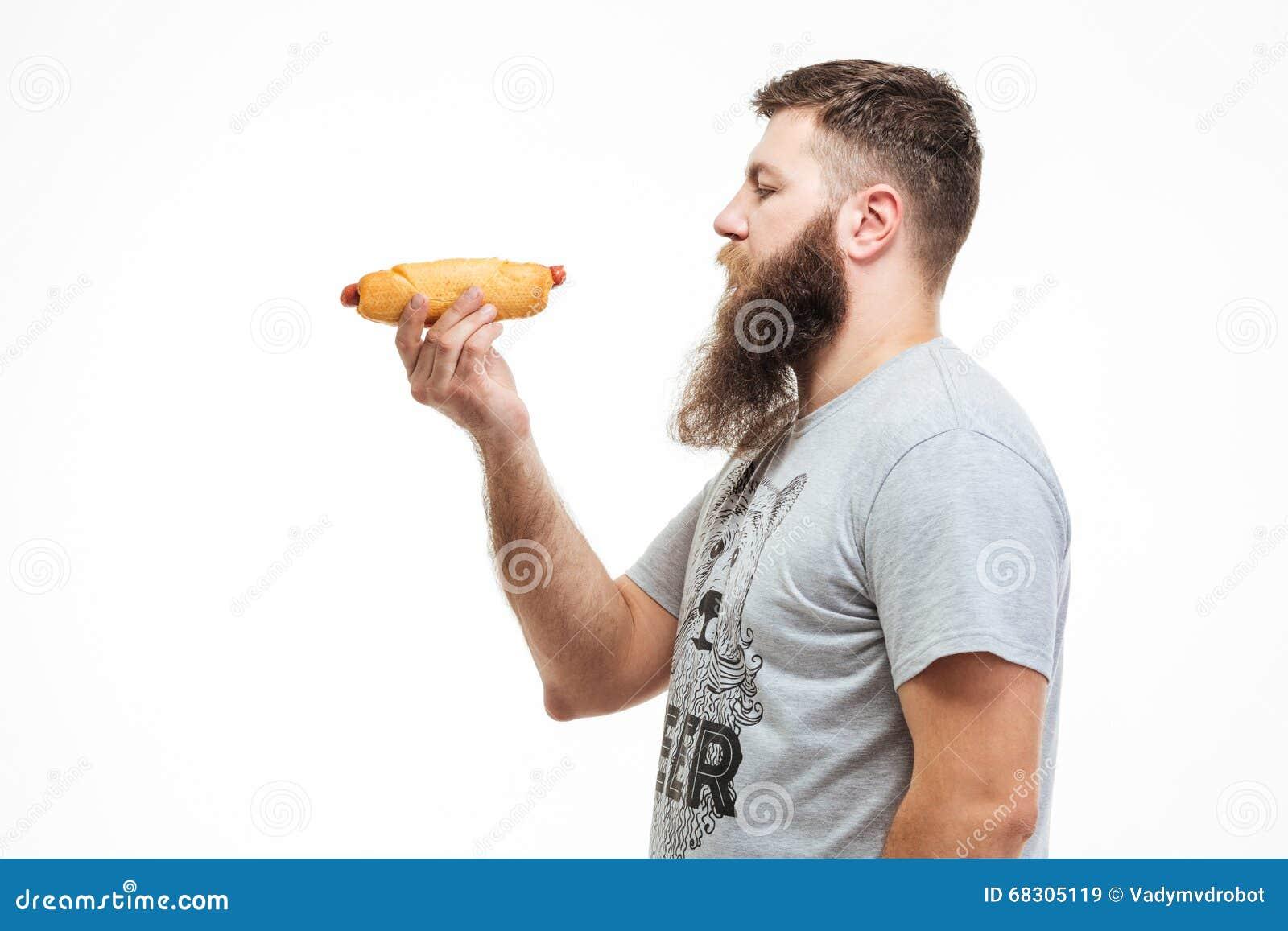 Hombre barbudo atractivo que coloca y que sostiene el perrito caliente