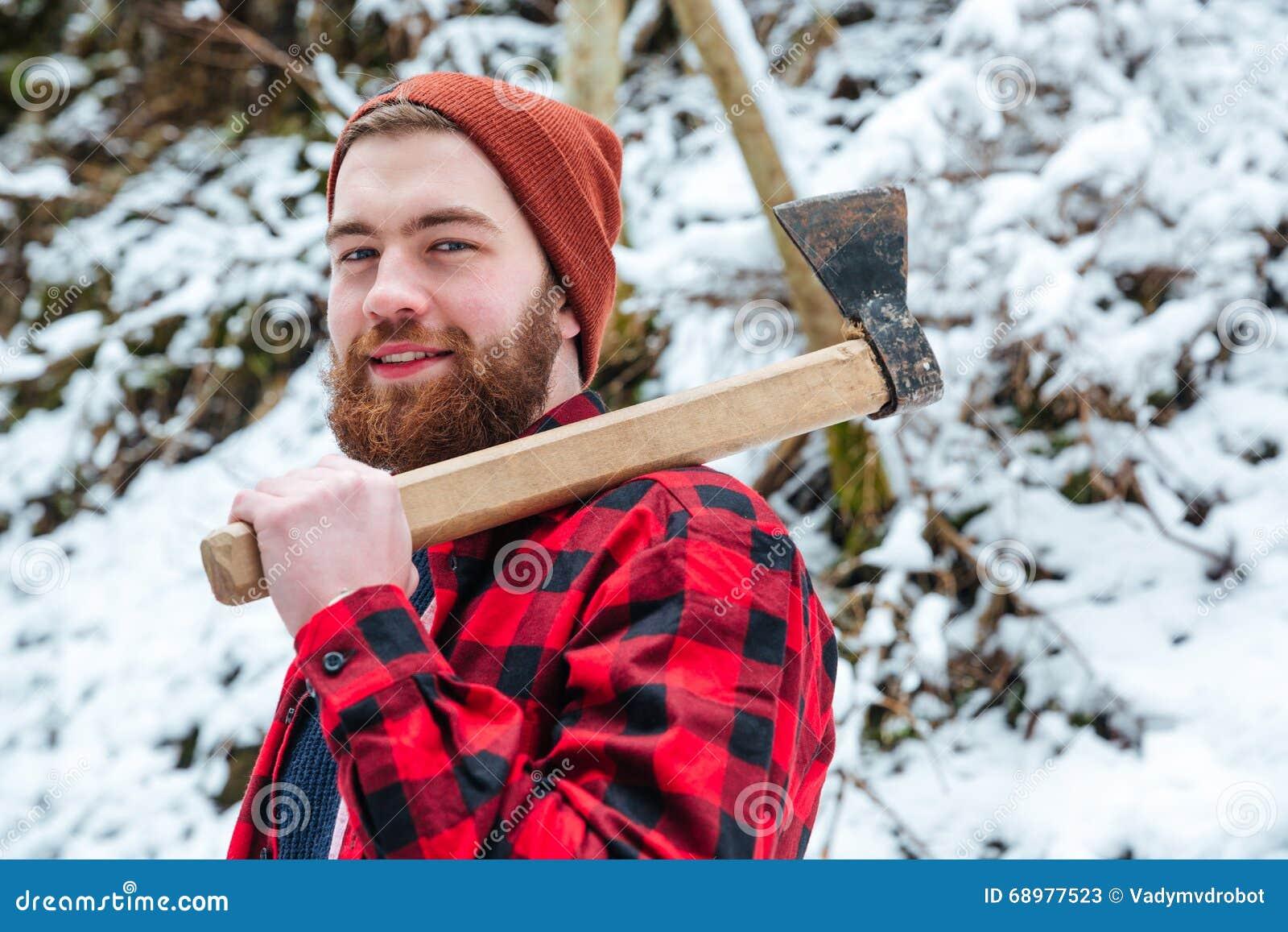 Hombre barbudo atractivo sonriente con el hacha en bosque del invierno