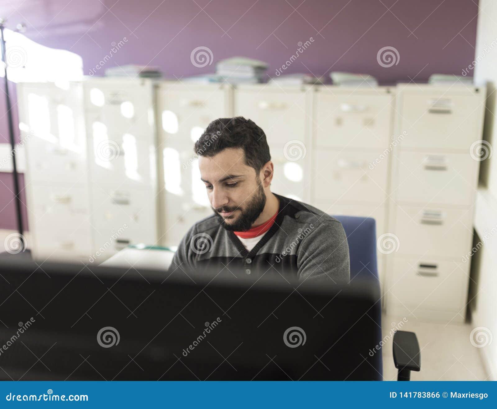 Hombre barbudo casual que trabaja en la oficina
