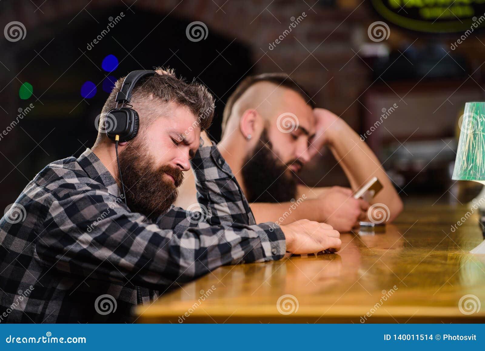Hombre barbudo del inconformista pasar ocio en el contador de la barra Bebidas de la orden en el contador de la barra Hombres con
