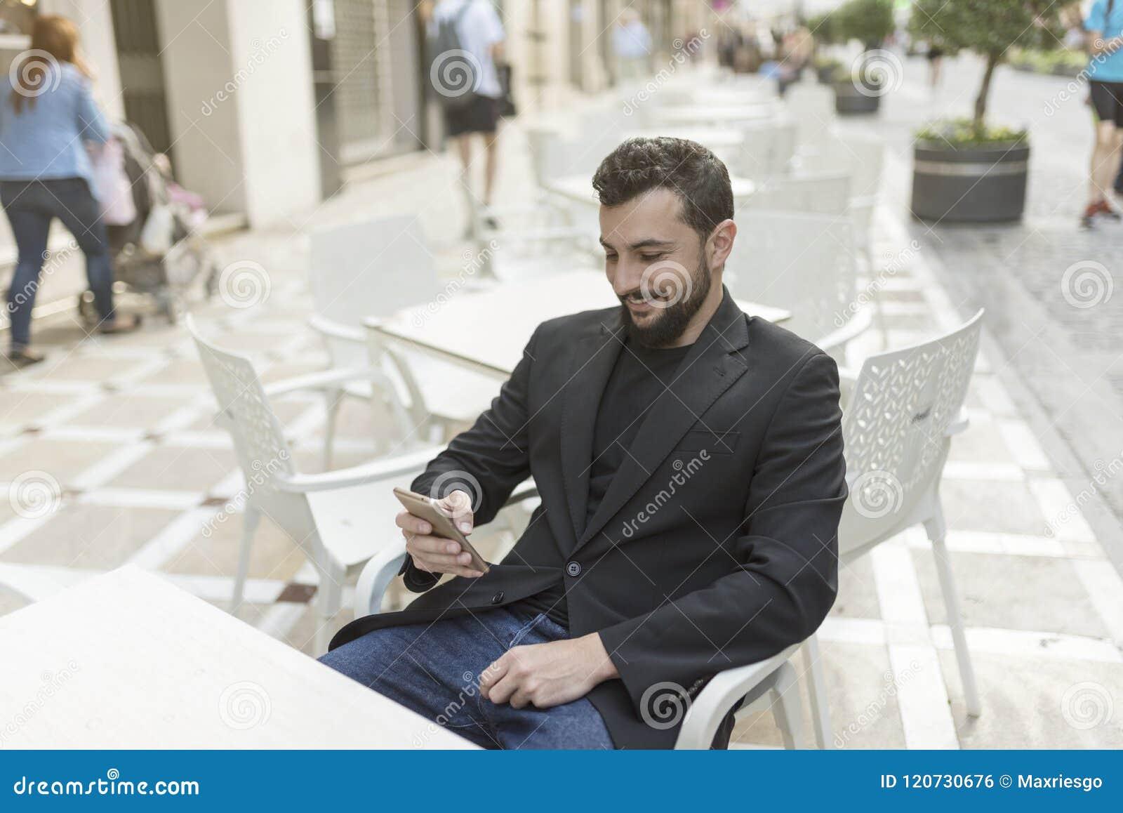 Hombre barbudo del traje en la terraza de la barra que mira smartphone y la sonrisa