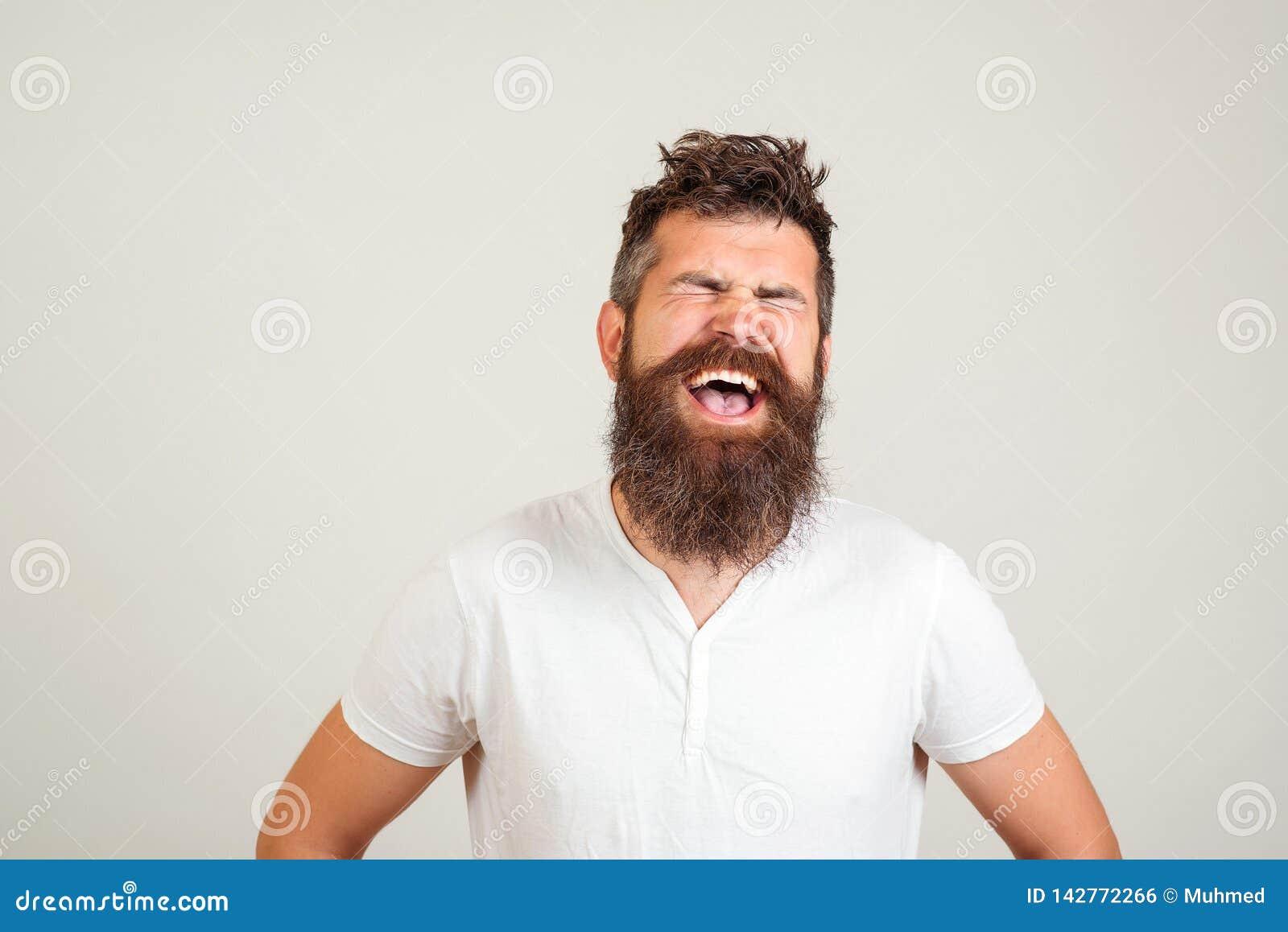 Hombre barbudo feliz elegante con los ojos cerrados que grita en el fondo blanco El varón excitó la expresión de la cara E