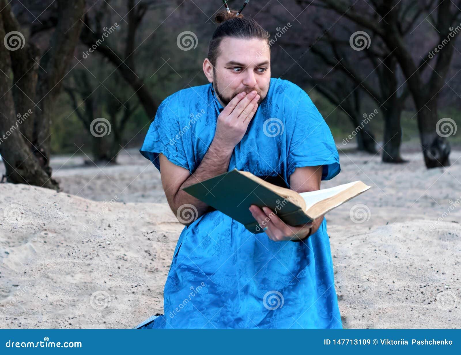 Hombre barbudo hermoso chocado en libro azul de la sentada y de lectura del kimono
