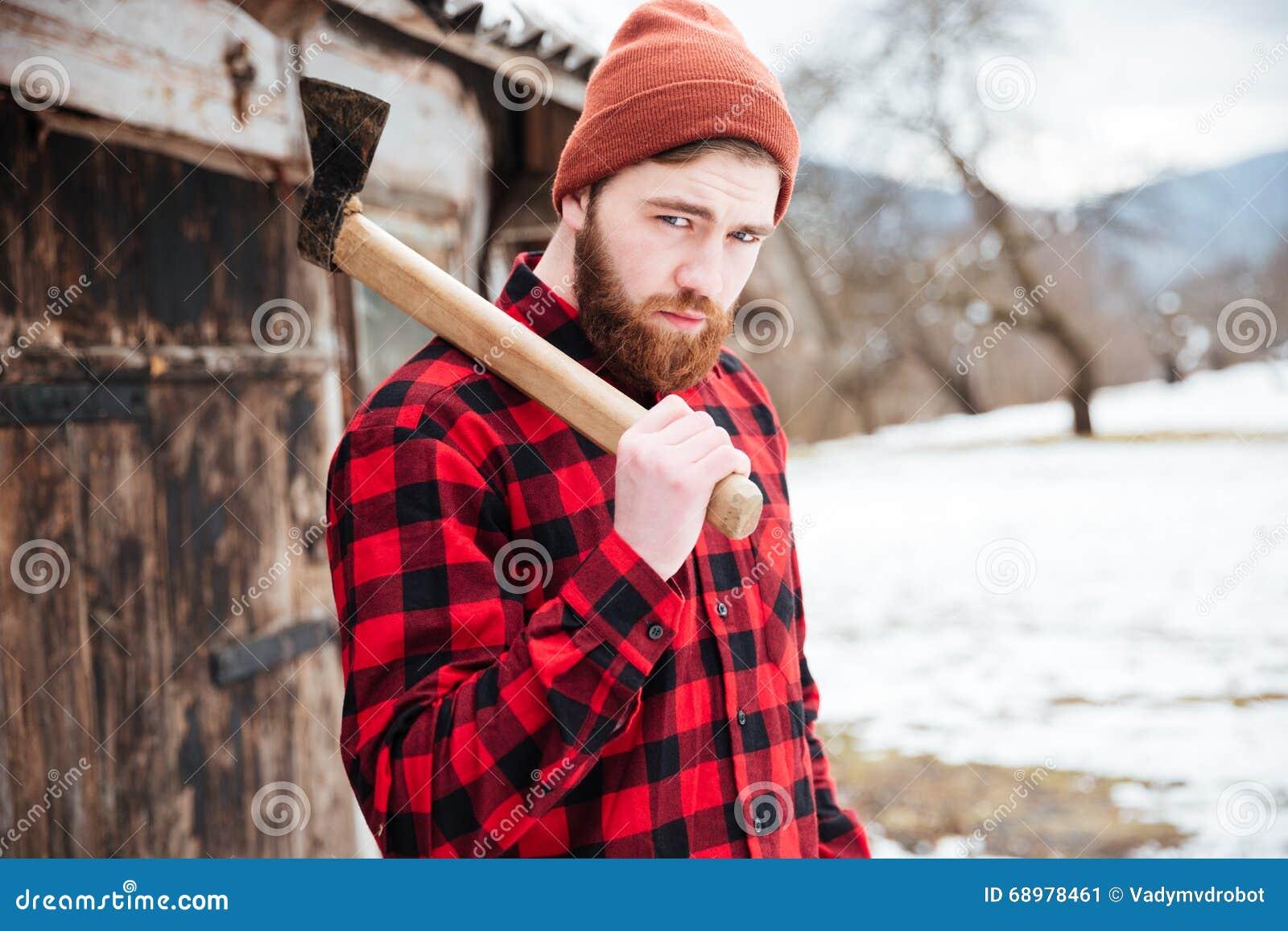 Hombre barbudo hermoso con el hacha en pueblo