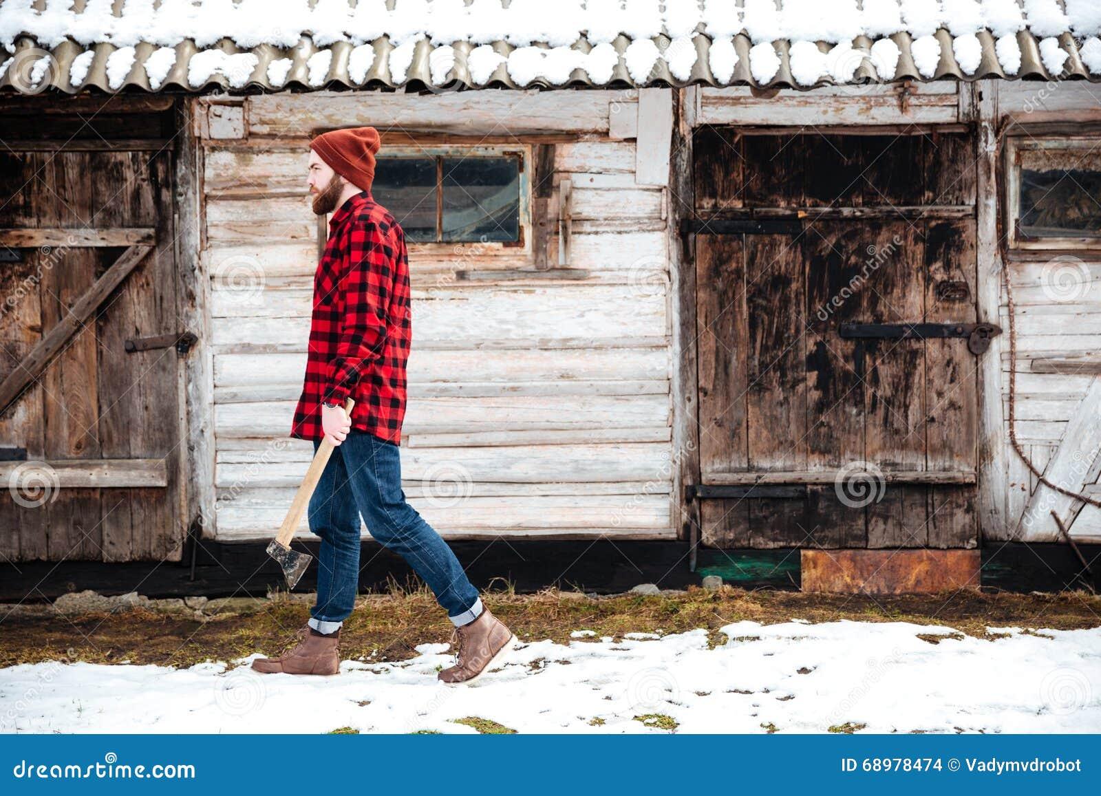 Hombre barbudo hermoso que sostiene el hacha y que camina en pueblo