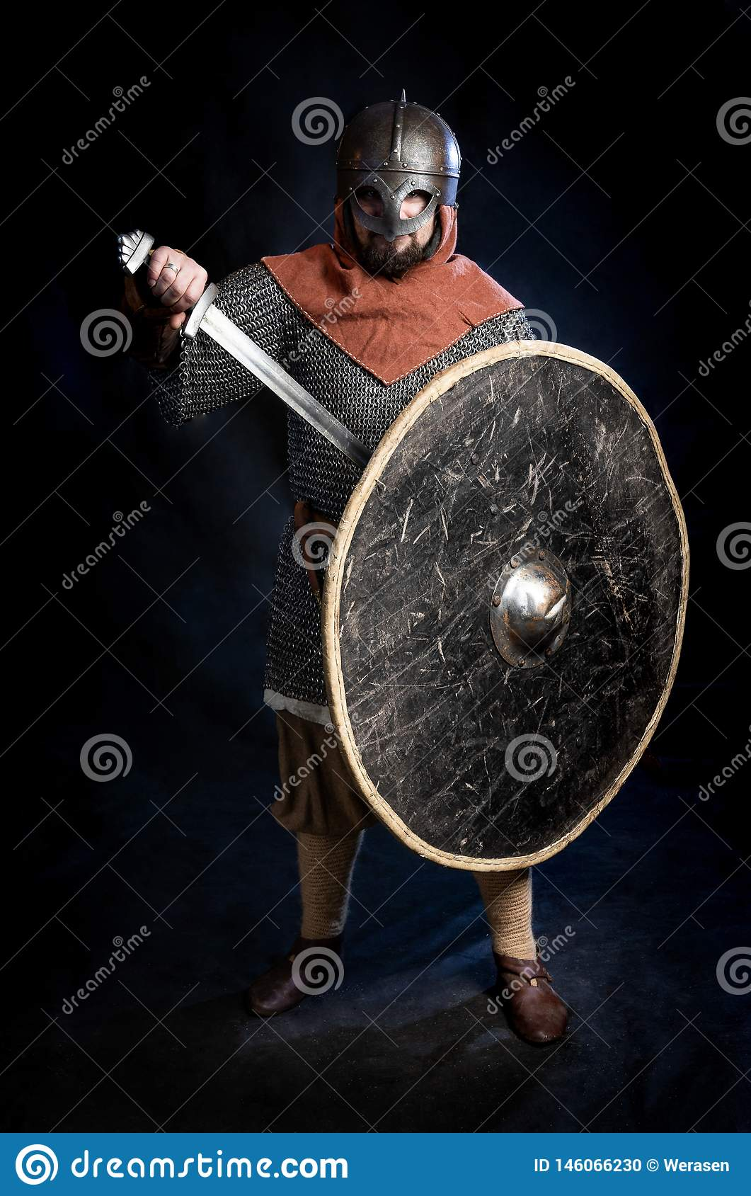 Hombre barbudo joven en un standind y sostener del casco de la Viking-era una espada y un escudo