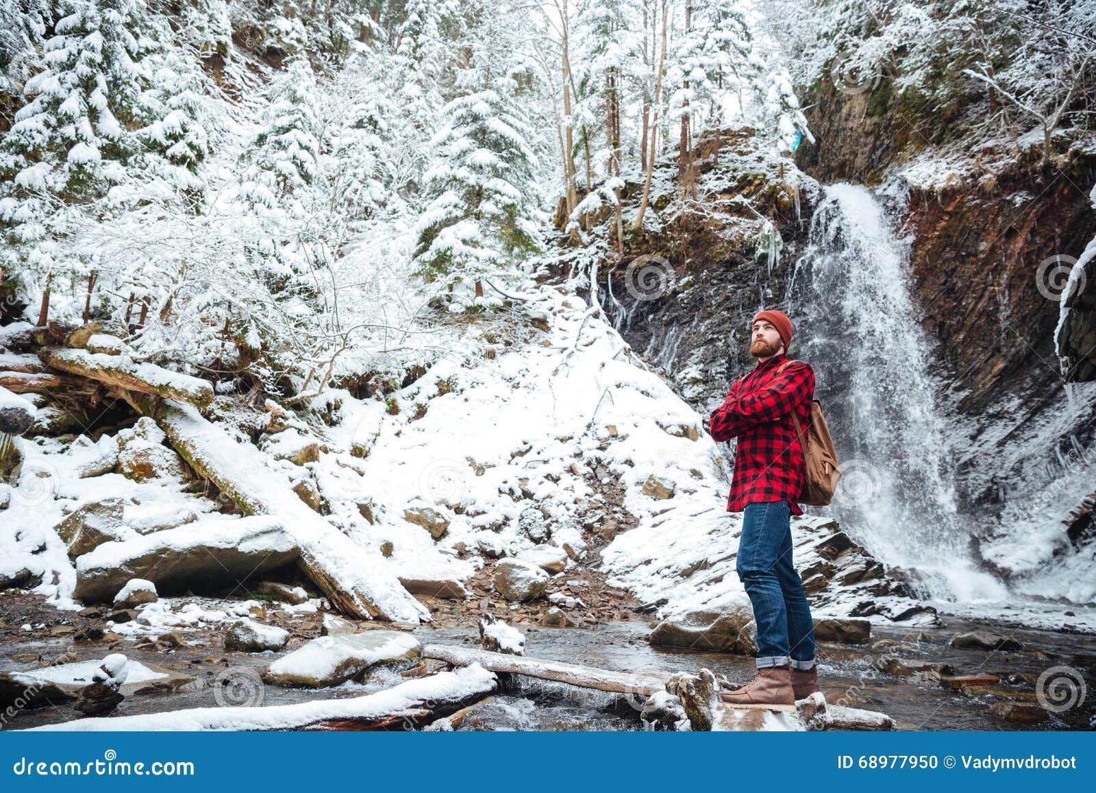 Hombre barbudo pensativo stading cerca de la cascada en las montañas en invierno