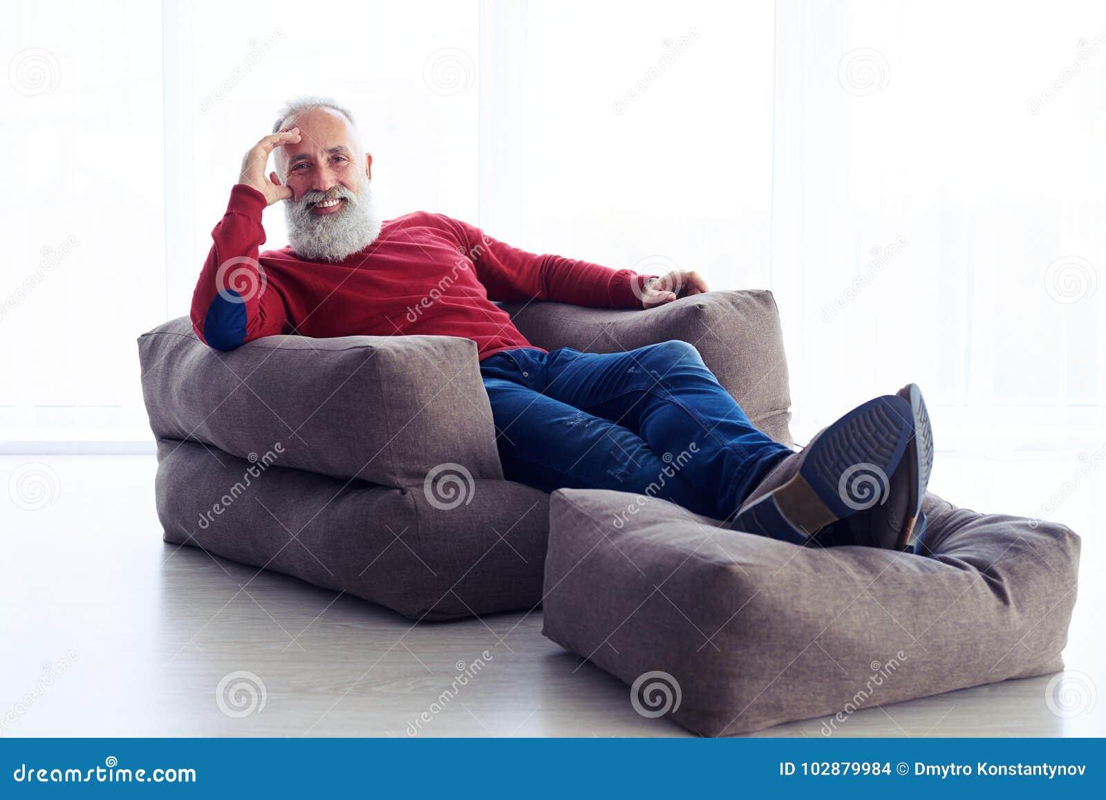 Hombre barbudo relajado que se sienta en butaca al lado de la ventana en ho
