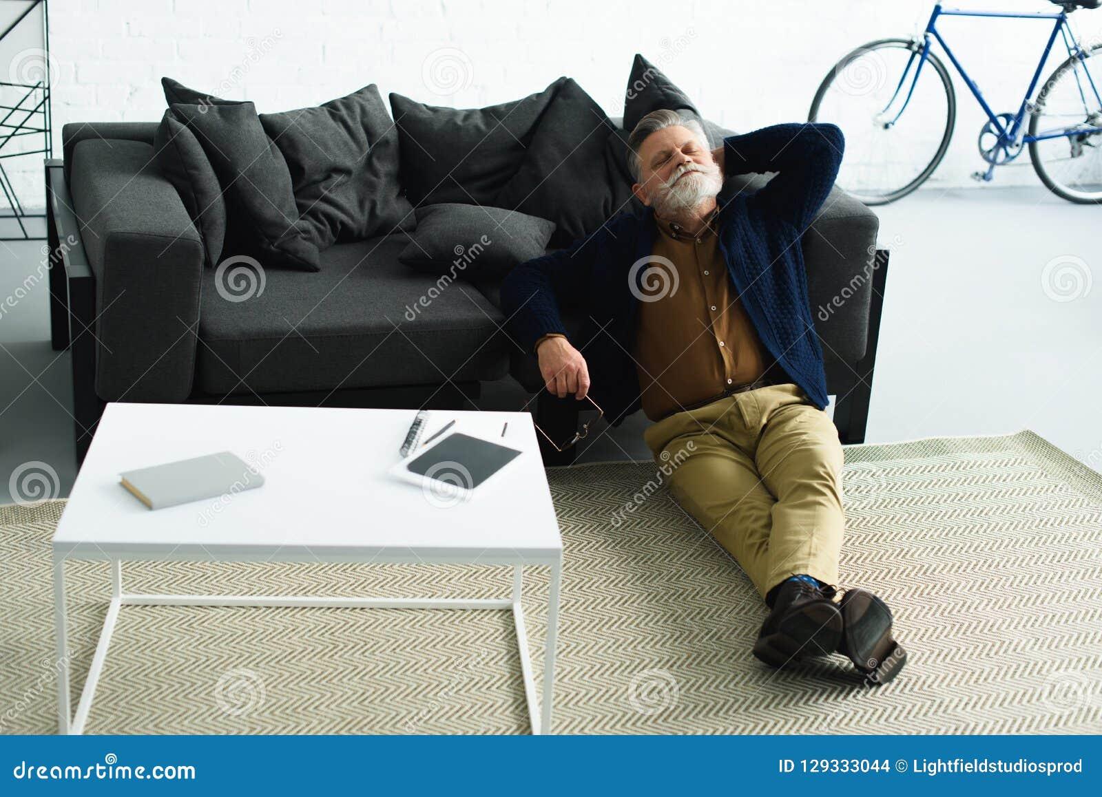 Hombre barbudo relajado que se sienta en la alfombra y que se inclina en el sofá