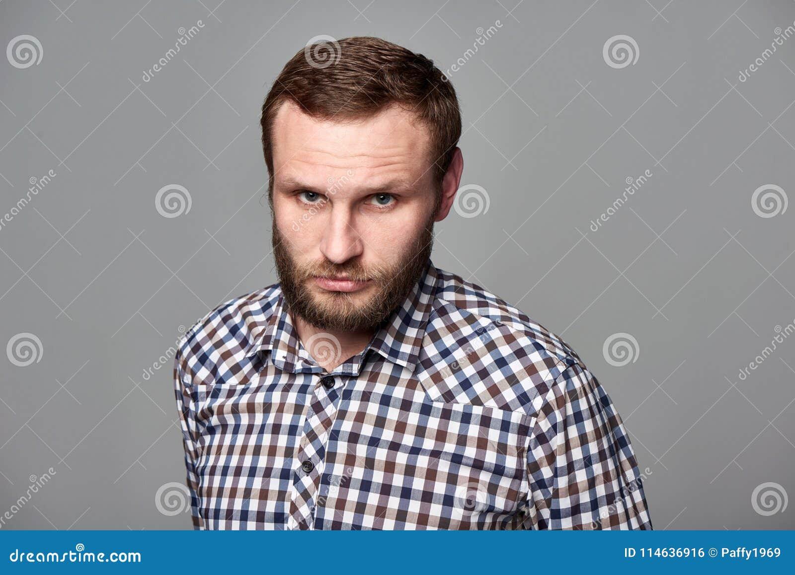 Hombre barbudo severo en camisa a cuadros