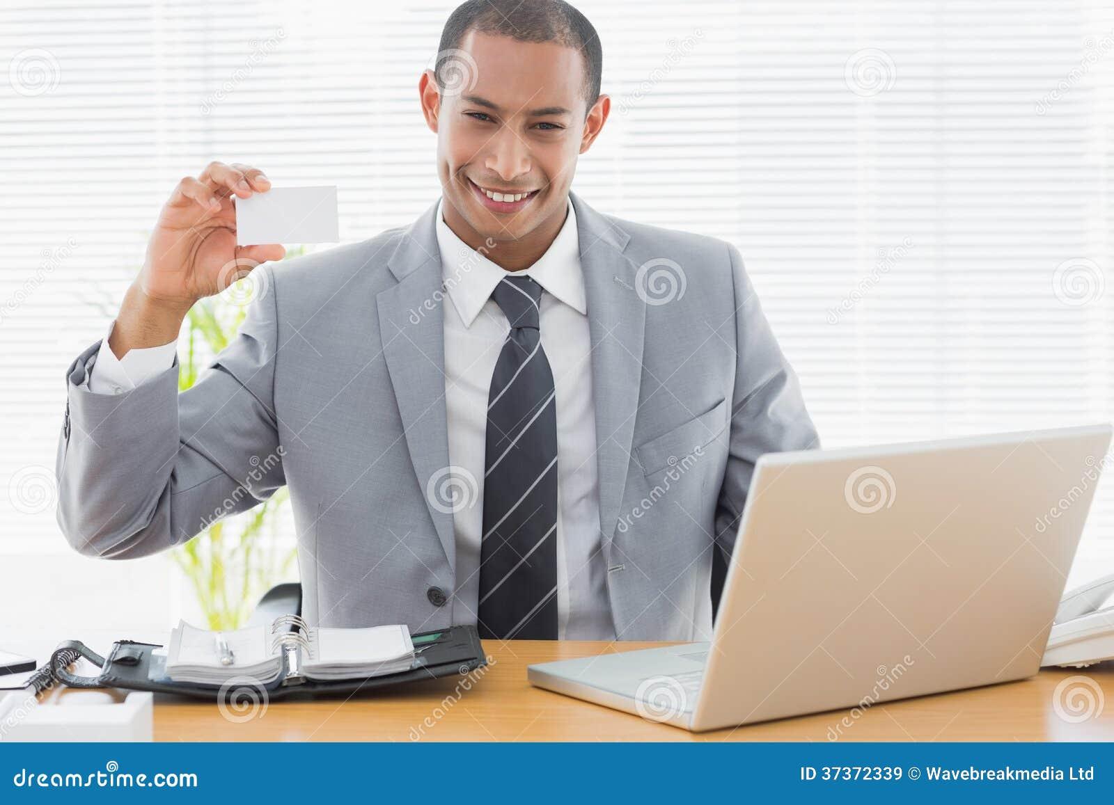 Hombre bien vestido confiado con la tarjeta de visita en el escritorio de oficina