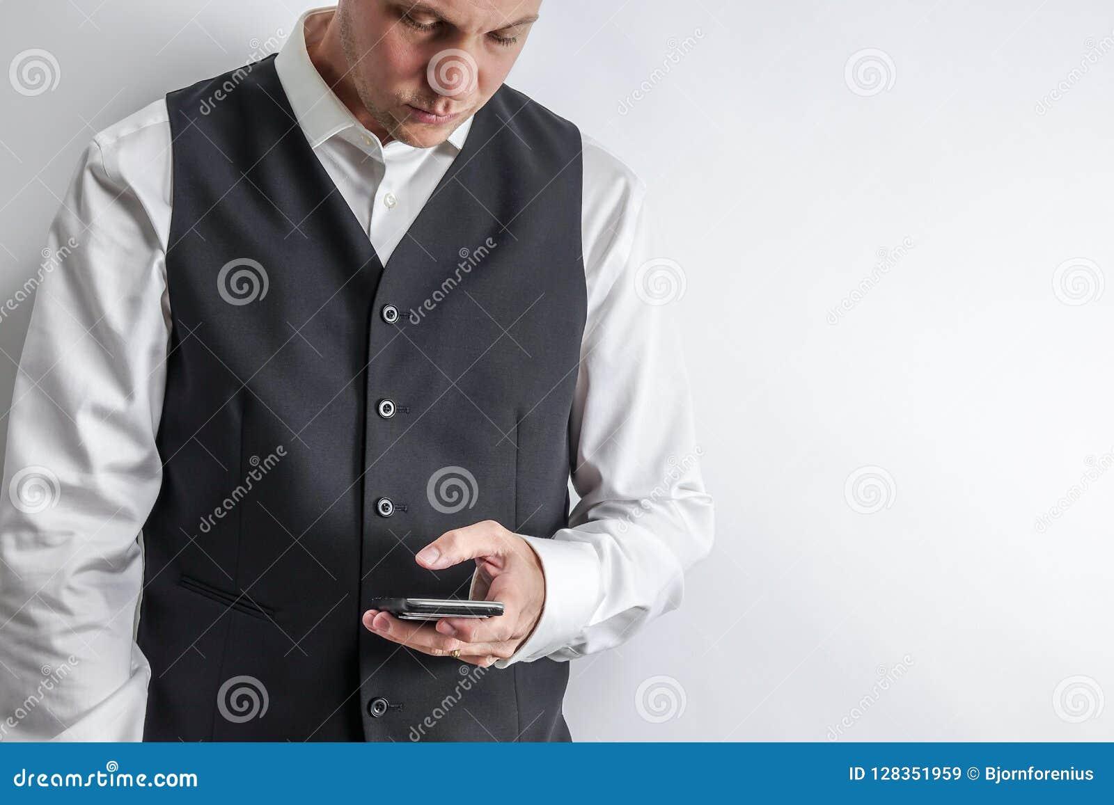 Hombre bien vestido loooking en su teléfono elegante