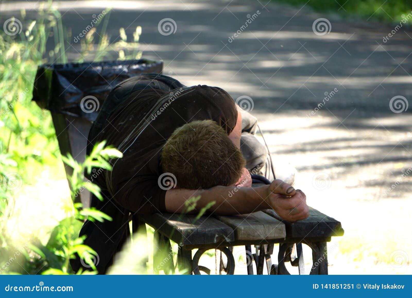 Hombre borracho que duerme en parque en banco de madera