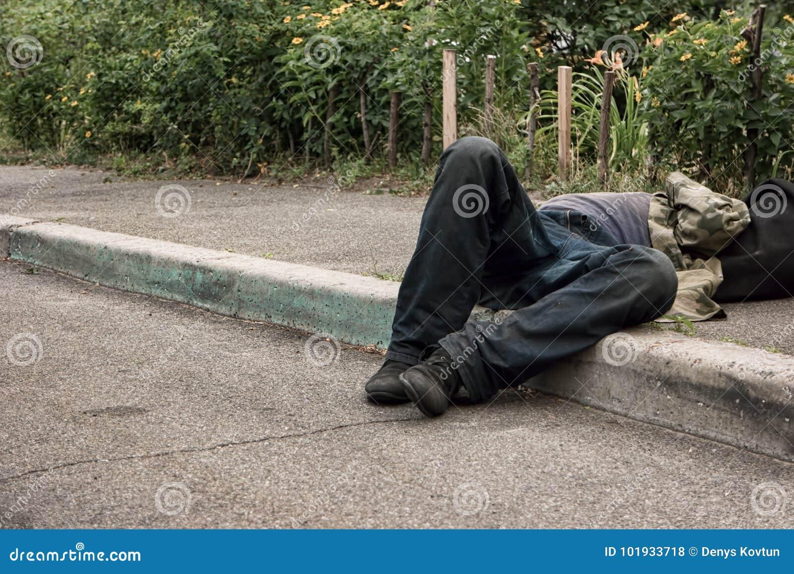 Hombre borracho que miente en el pavimento