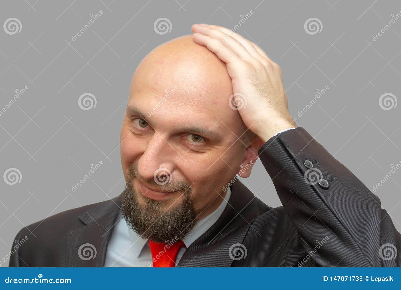 Hombre calvo en traje, cabeza afeitada, fondo gris