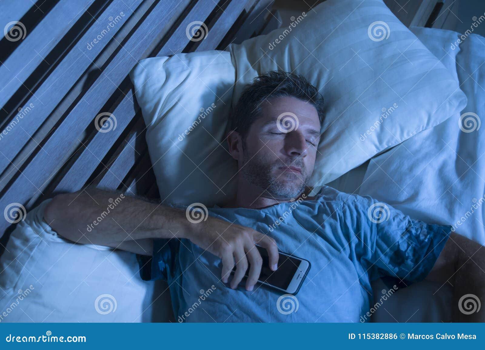 Hombre cansado atractivo en caer de la cama dormido mientras que usa el teléfono móvil todavía que sostiene el celular en su mano