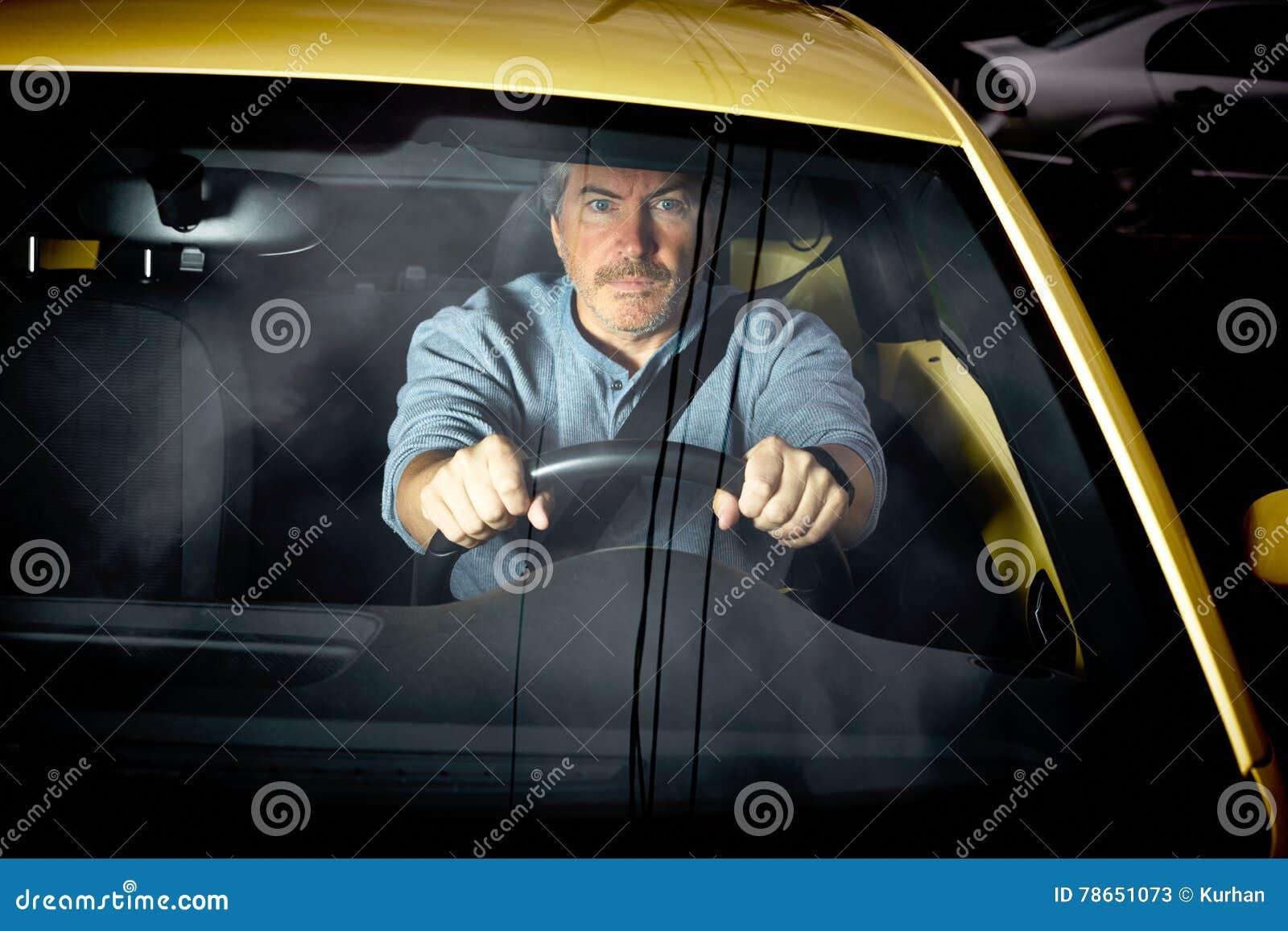 Hombre cansado que conduce el coche en la noche