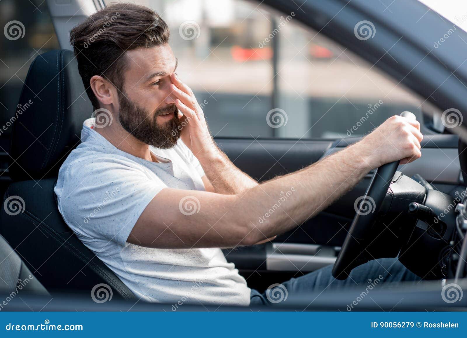Hombre cansado que conduce un coche