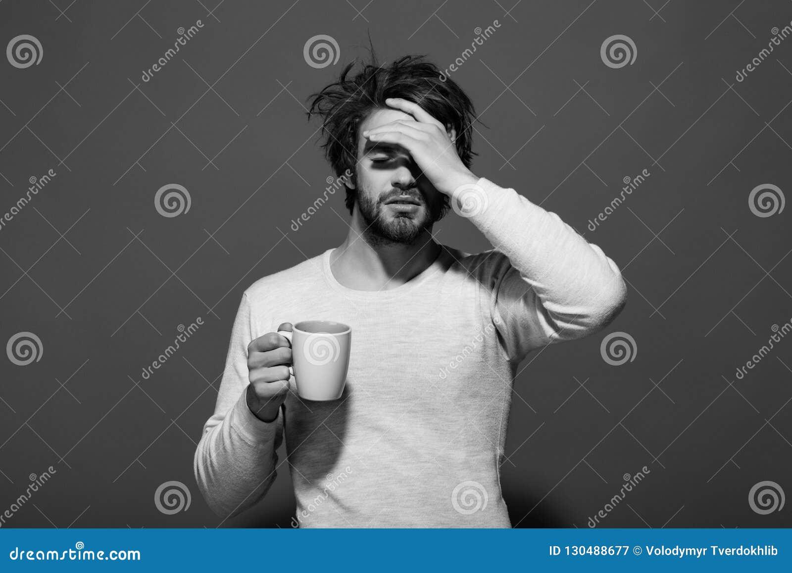 Hombre cansado soñoliento con la taza del control del dolor de cabeza de té