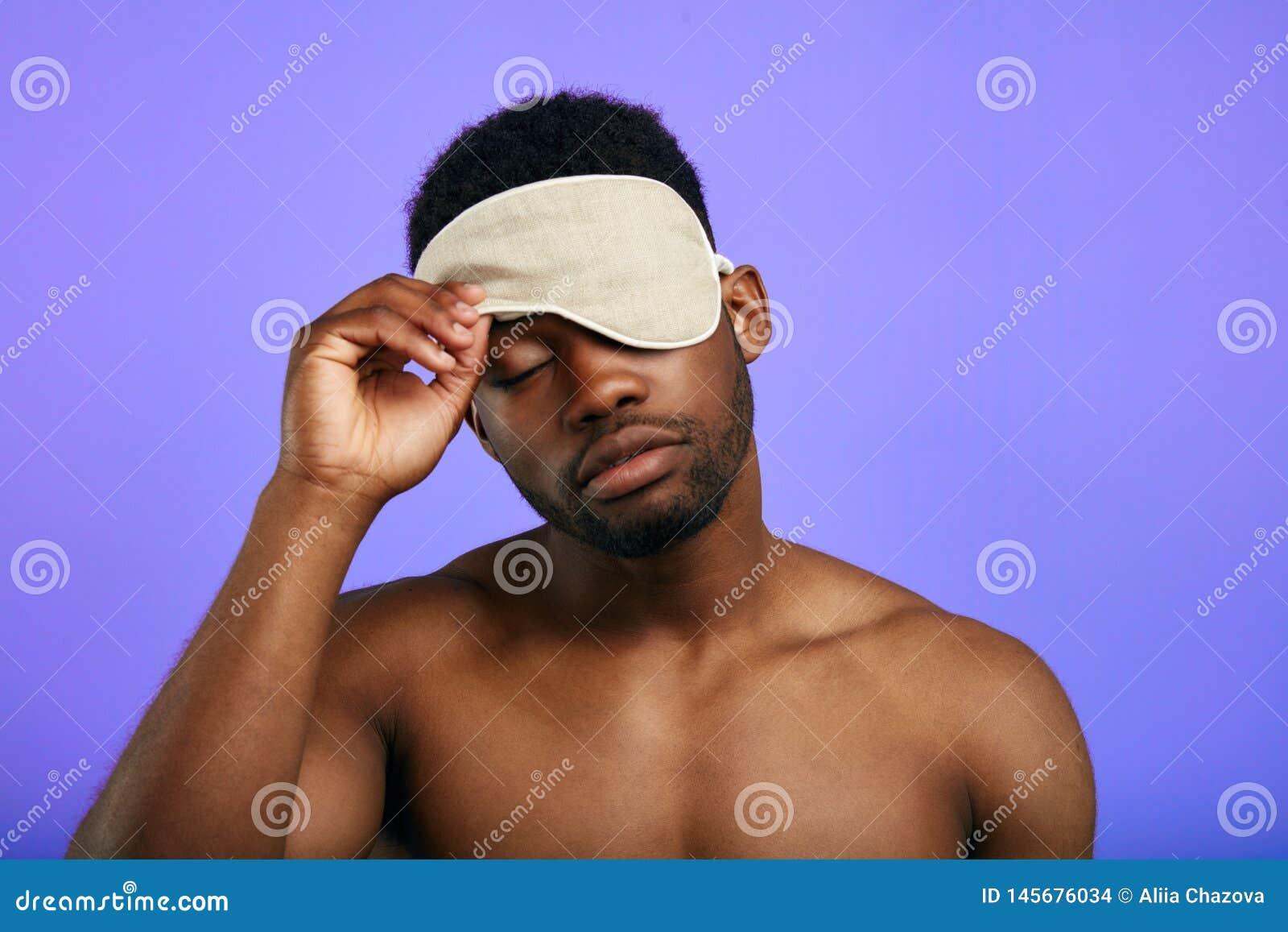 Hombre cansado soñoliento que saca o que pone en la máscara el dormir