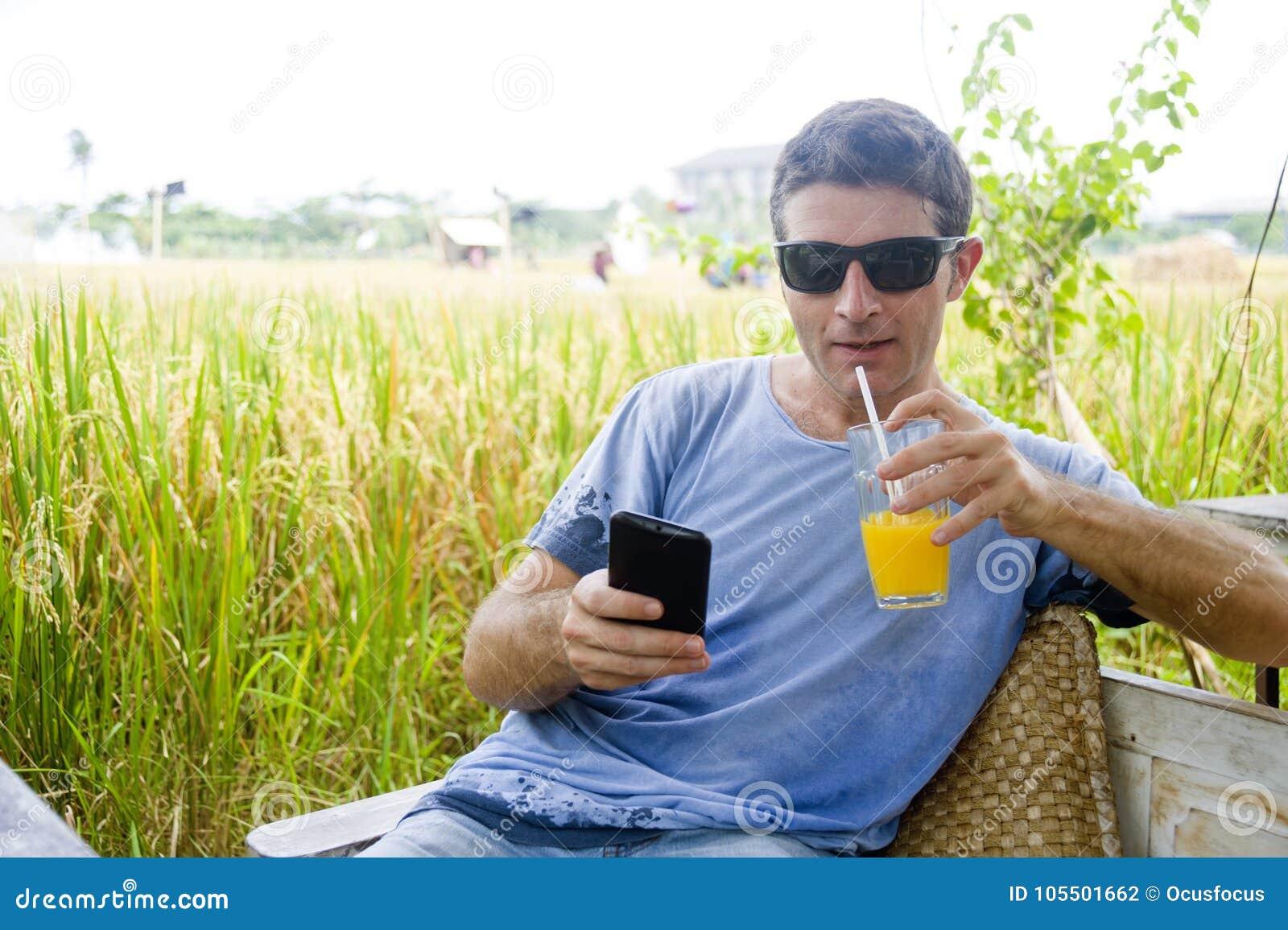 Hombre caucásico atractivo 30s que sonríe sentada feliz y relajada en la cafetería del campo del arroz en viaje del día de fiesta