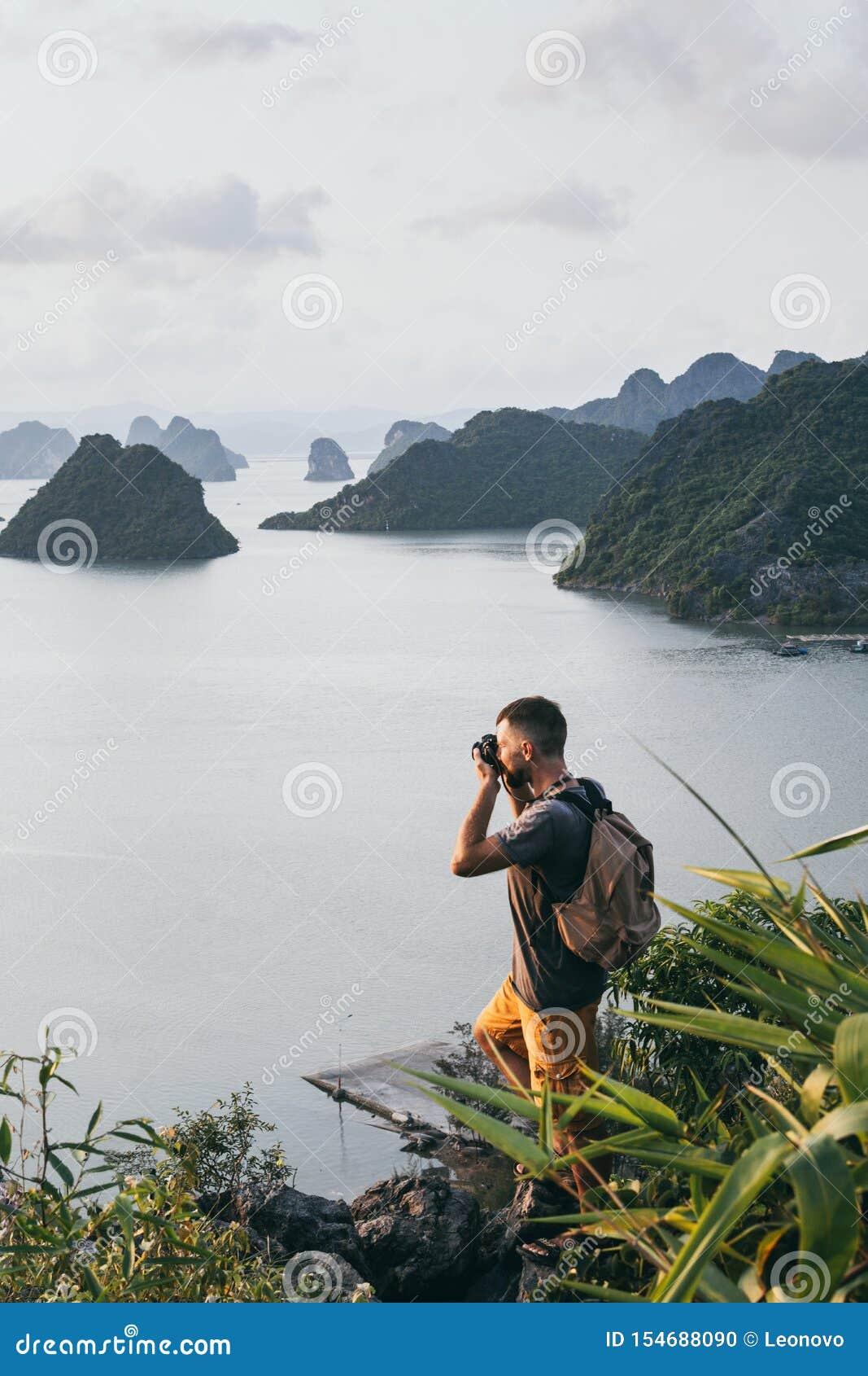 Hombre caucásico que hace una foto en un top de un acantilado que pasa por alto la bahía durante puesta del sol, Vietnam de Halon