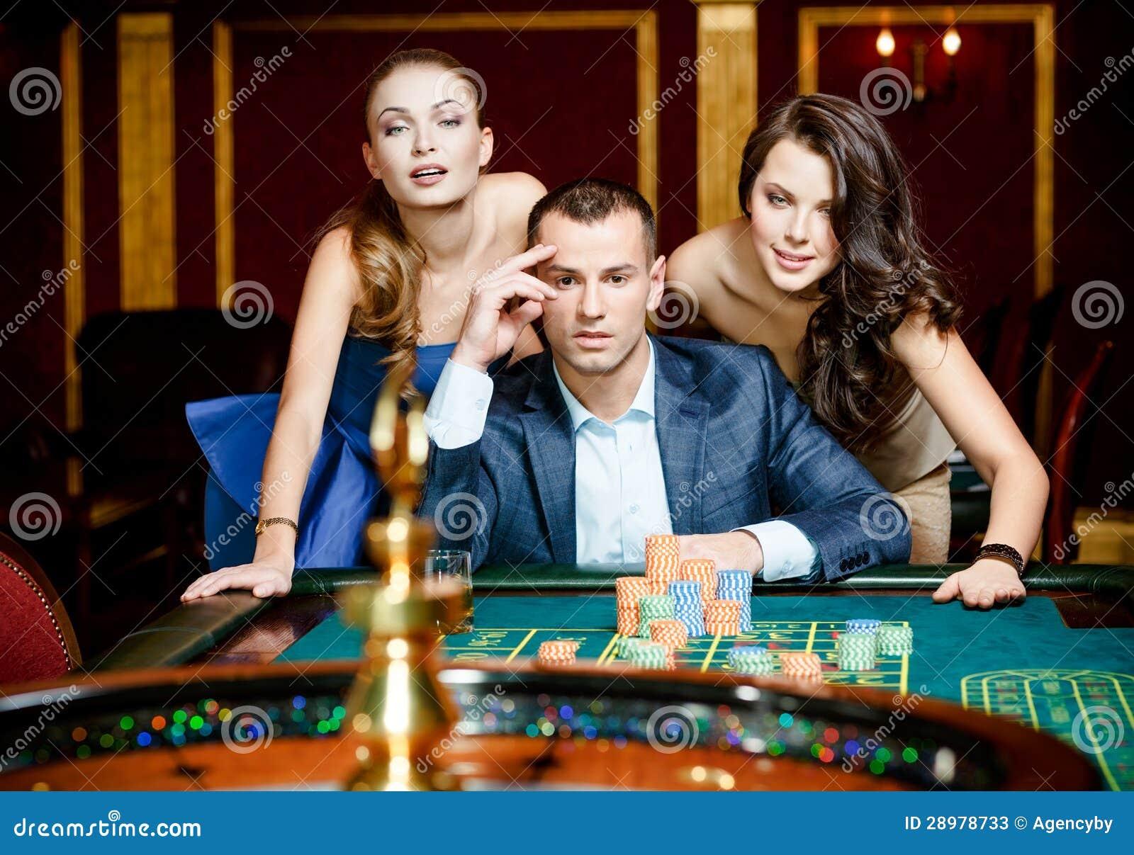 Hombre con dos señoras que juegan la ruleta en el casino