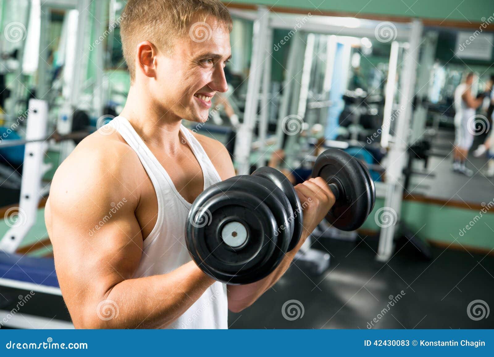 Hombre con el equipo de entrenamiento del peso