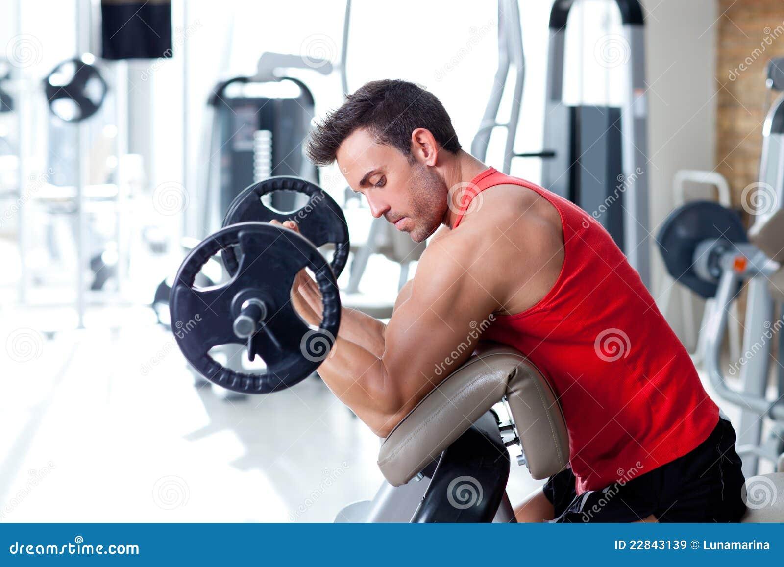 Hombre con el equipo de entrenamiento del peso en la gimnasia del deporte