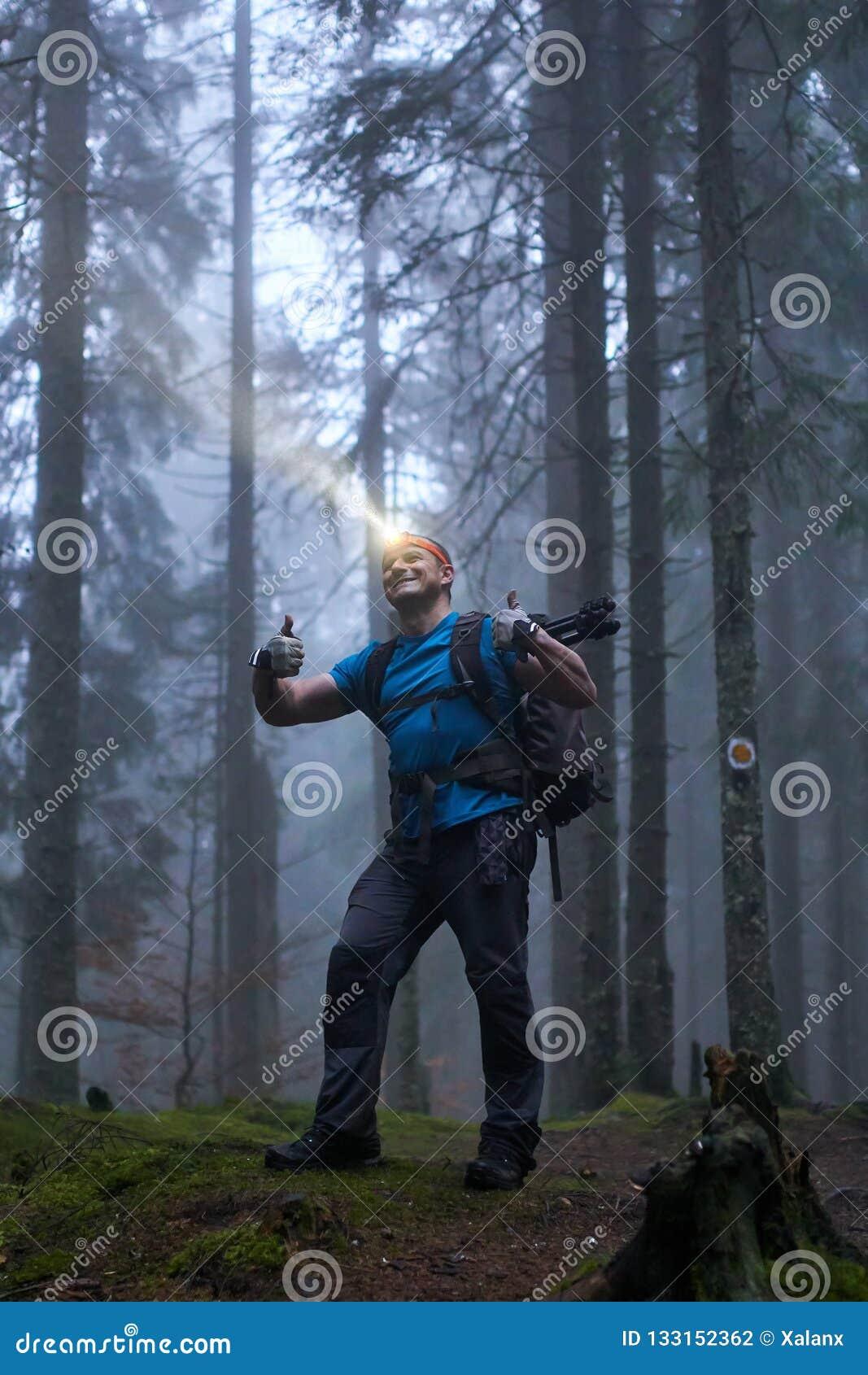 Hombre con el faro y la mochila en el bosque