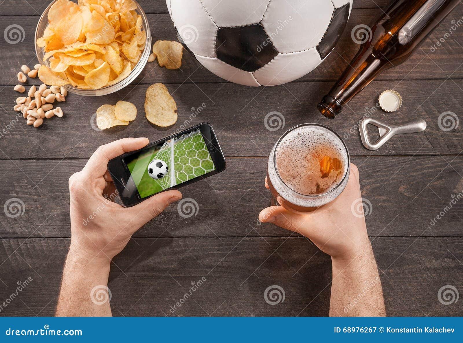 Hombre con el juego de fútbol de observación de la cerveza en smarphone