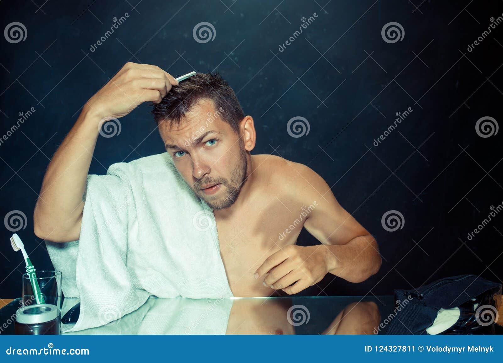 Hombre con el peine referido sobre pérdida de pelo