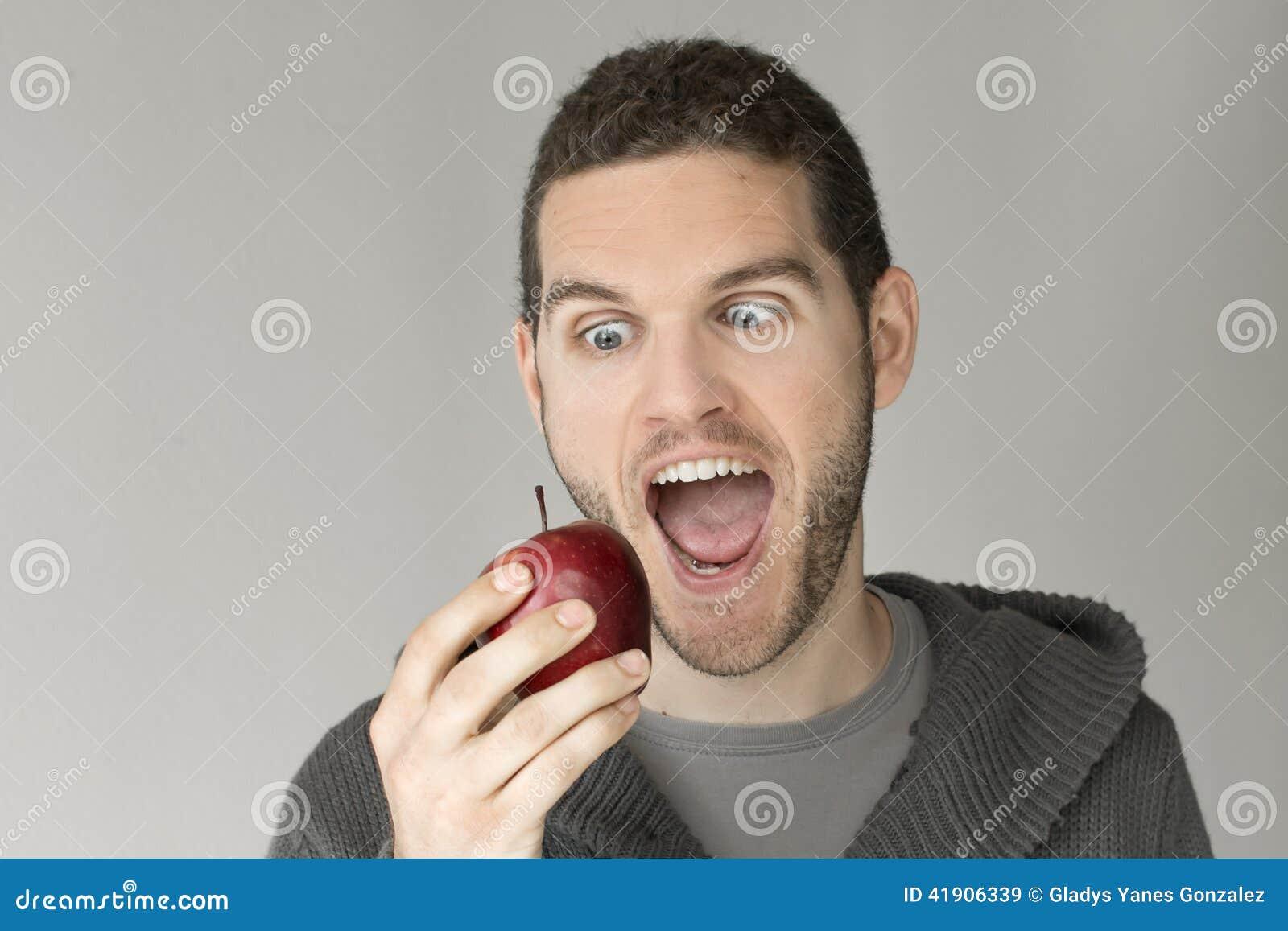 Hombre con la cara divertida que mira una manzana