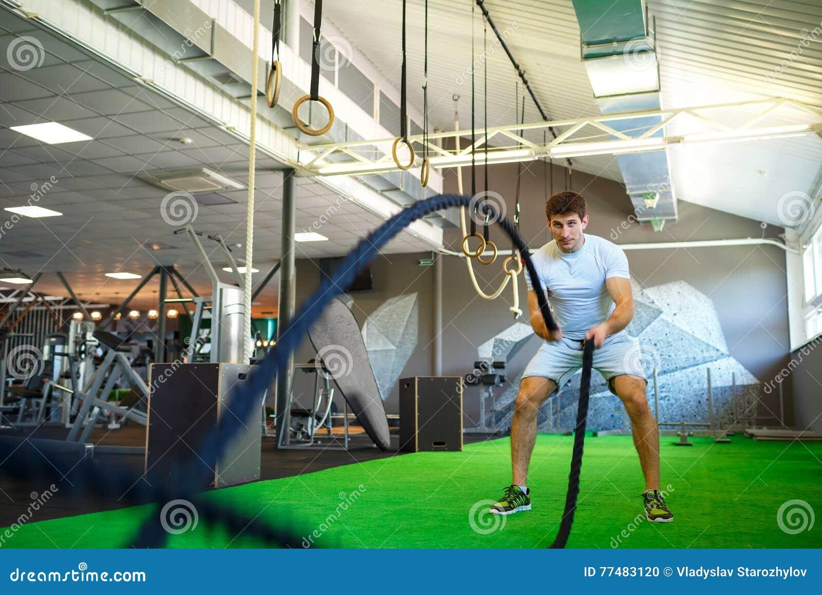 Hombre con la cuerda de la batalla en gimnasio funcional de la aptitud del entrenamiento