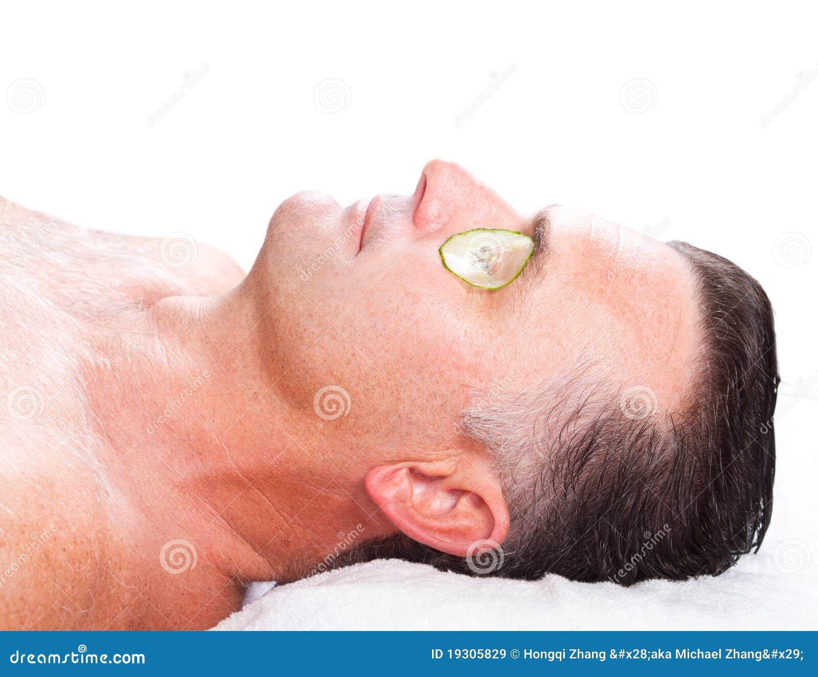 Hombre con la máscara del facial del pepino