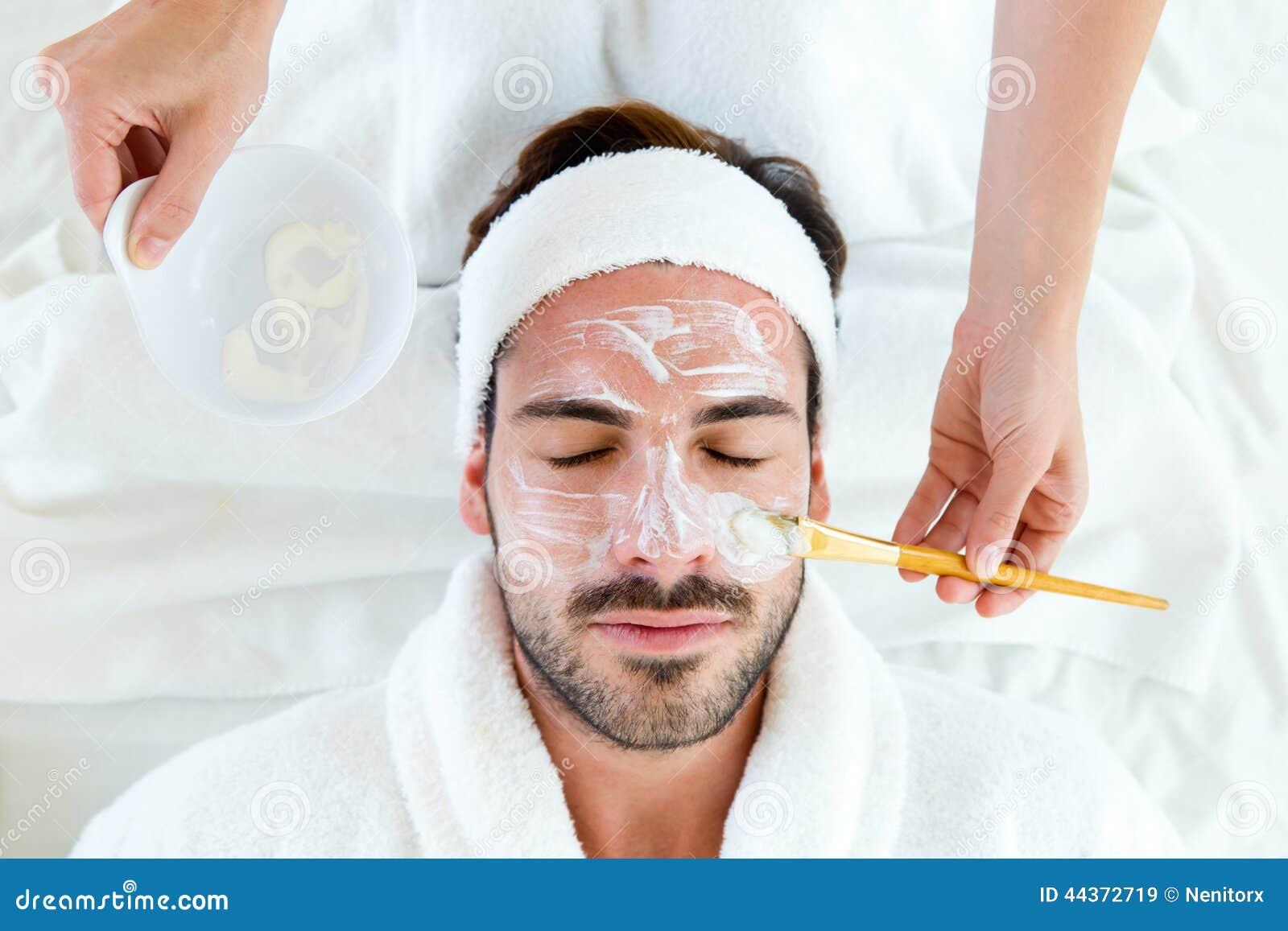 Hombre con la máscara facial de la arcilla en balneario de la belleza