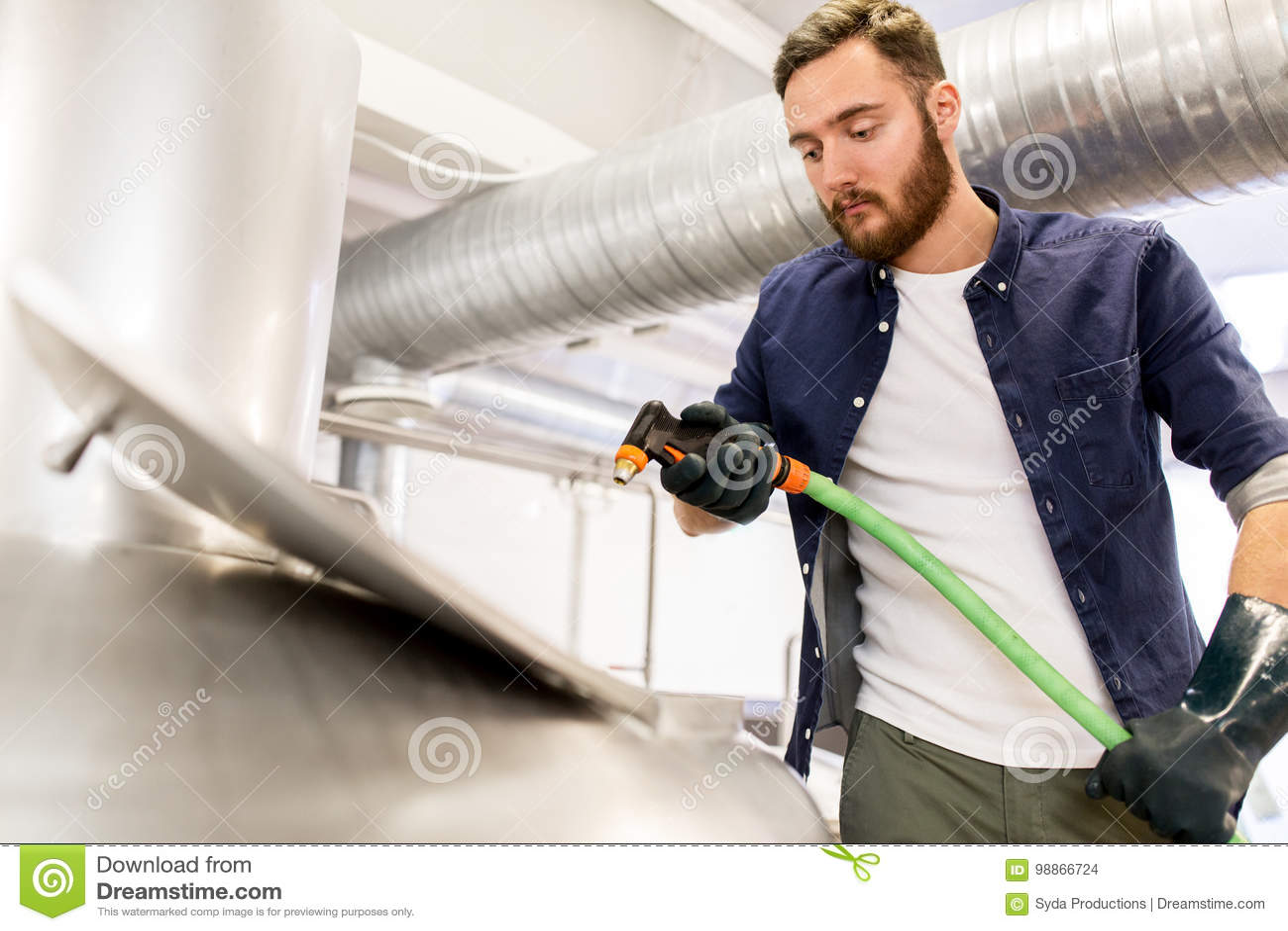 Hombre con la manguera que trabaja en la caldera de la cervecería de la cerveza del arte