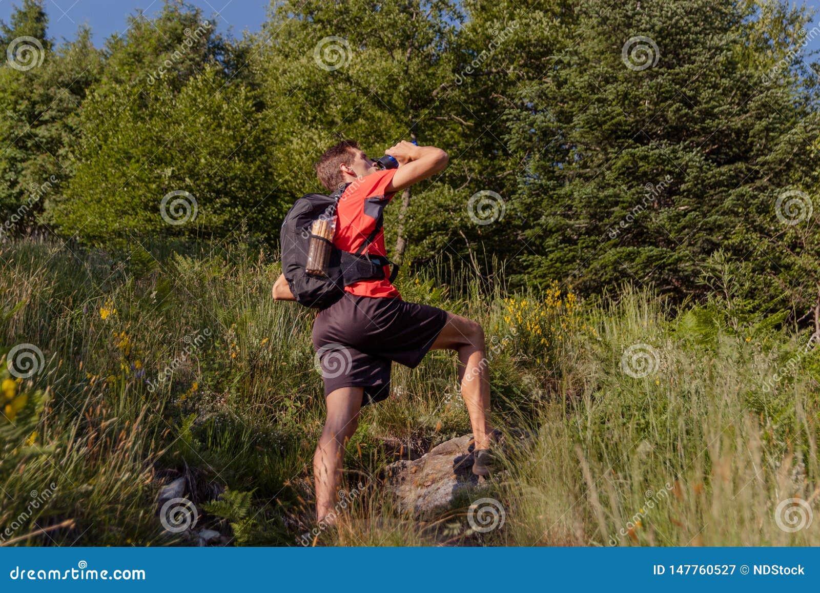 Hombre con la mochila tomar un resto y la consumición de la botella de agua durante un alza